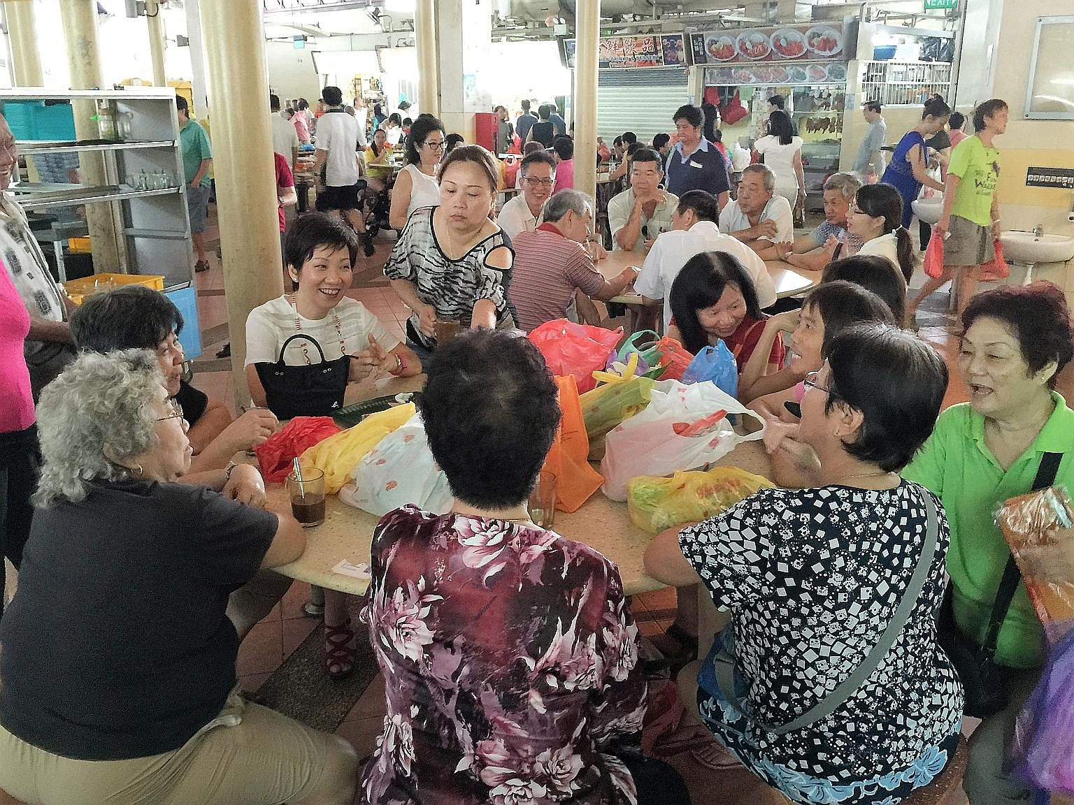 Minister for Culture, Community and Youth Grace Fu (third from left) chatting with residents at Yuhua Market and Hawker Centre at Jurong East Avenue 1. When sharing a table with residents, one finds out how the others are doing, such as how many gran