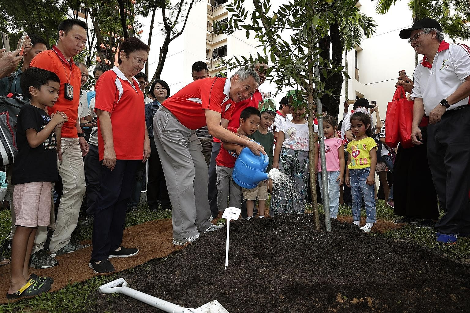 Prime Minister Lee Hsien Loong watering a tree he planted in front of Block 405A Fernvale Lane in Sengkang at an annual tree-planting event yesterday. 	He and his fellow Ang Mo Kio GRC MPs - Dr Koh Poh Koon, Mr Ang Hin Kee and Mr Gan Thiam Poh - as w