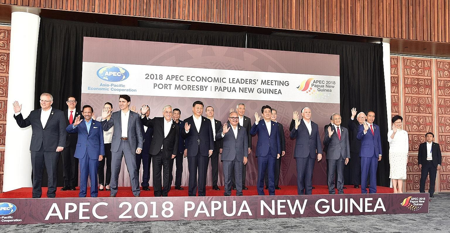 Prime Minister Lee Hsien Loong listening to a presentation at the Apec summit in Port Moresby yesterday. He called on fellow leaders to press on with efforts to form a Free Trade Area of the Asia-Pacific.