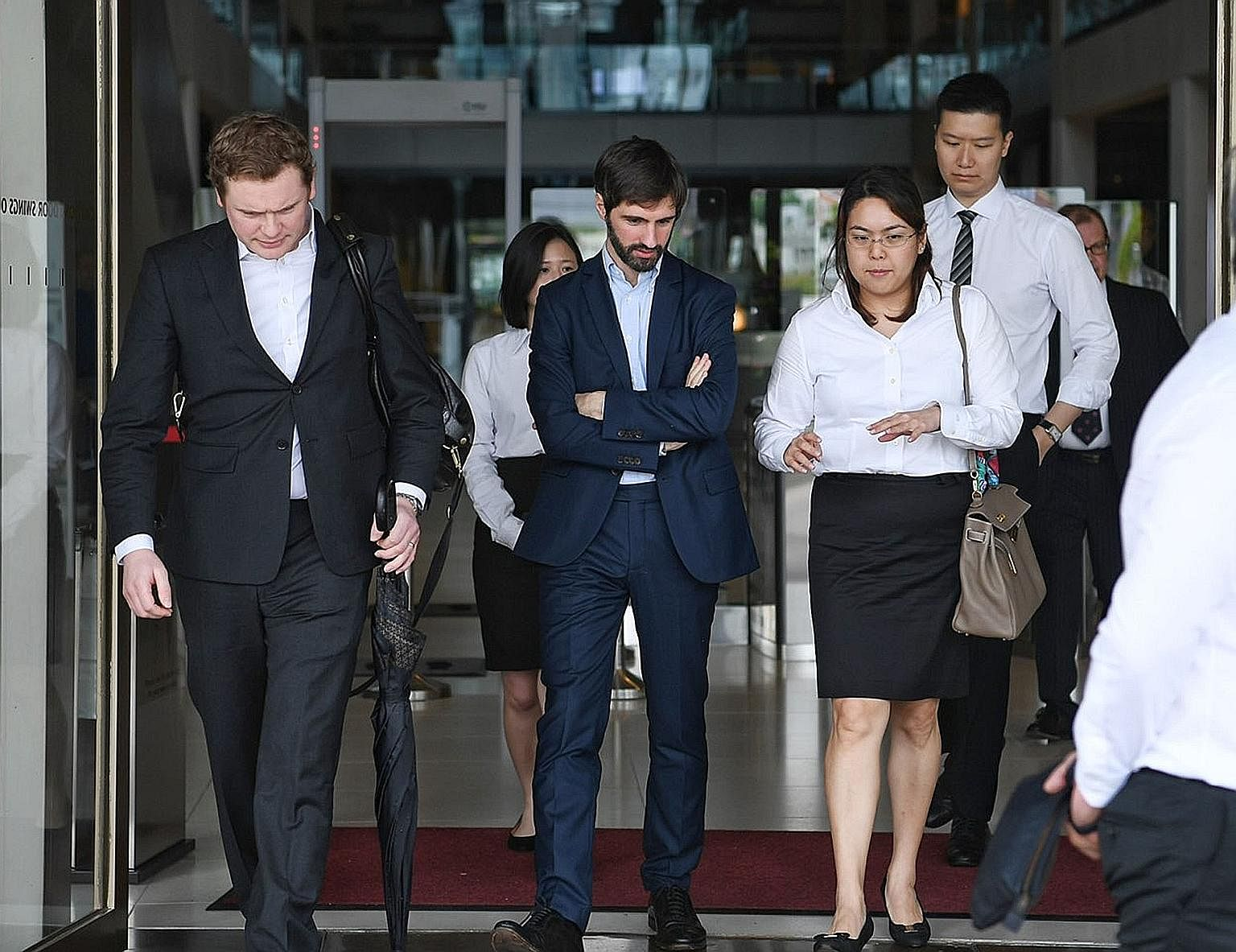 "B2C2 co-founder Maxime Boonen (centre), with his lawyers at the court yesterday. The electronic market maker is suing cryptocurrency exchange operator Quoine over a ""unilateral reversal"" of orders on its platform."
