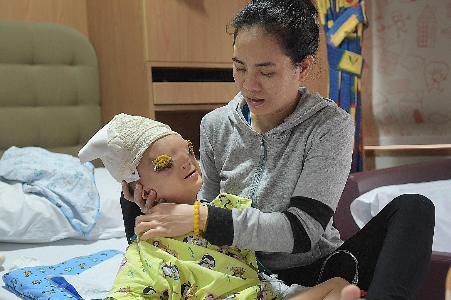Ton Nu Hoang Dung, seen here after surgery with her mother, Madam Hoang Thi Thuy Linh, was born with a rare deformity where a part of her brain protrudes from a gap in her skull into her face, pushing down her eyes. The medical team took on the case