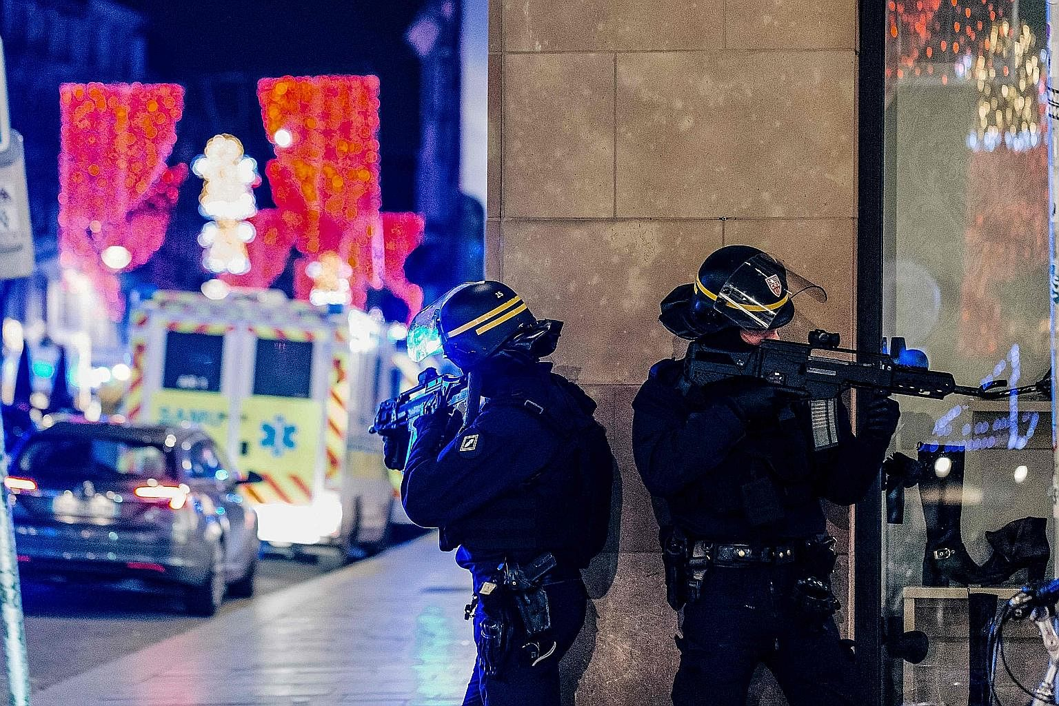 Police officers standing guard near the scene of a shooting on Tuesday in Strasbourg, eastern France, where a manhunt was launched for a gunman who killed at least two people near the city's famed Christmas market. Police identified the suspect as re