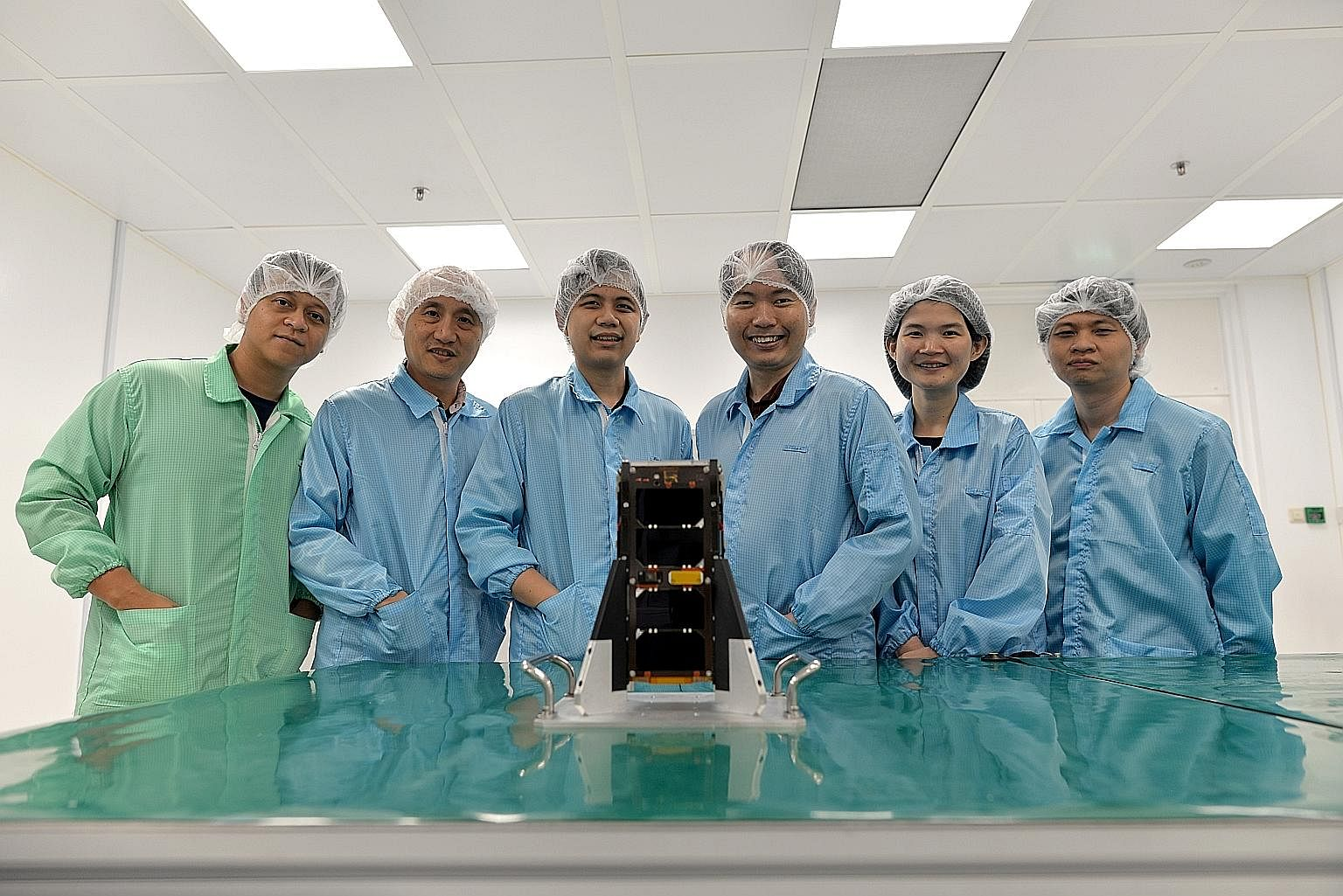 NTU Satellite Research Centre team members (from left) Richard Bui, Lim Sir Yang, Lew Jia Min, Joshua Tay, Amy Wong and Benjamin Tan with the Aoba-Velox IV nanosatellite, which will be launched in Japan later this month. They are learning from and im