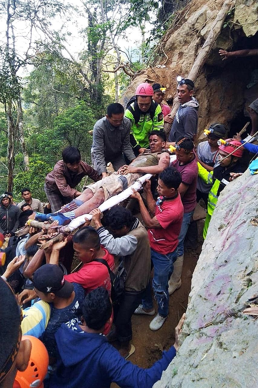 An Antara Foto picture showing rescue workers carrying the body of a victim after the collapse of an illegal gold mine in Bolaang Mongondow, North Sulawesi, on Tuesday. Rescuers moving a survivor to safety yesterday. Three people have been found dead