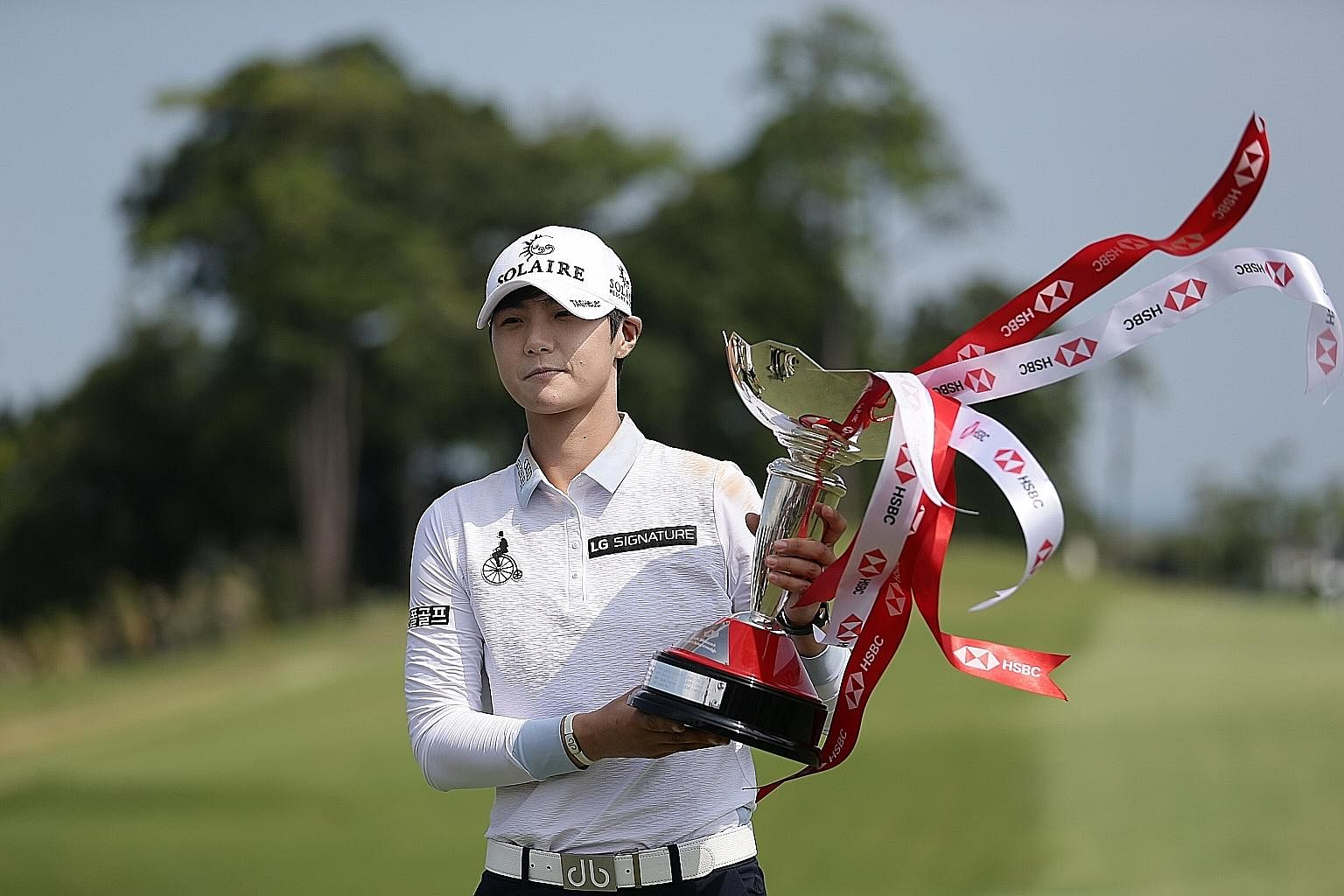 South Korean golfer Park Sung-hyun showing off her HSBC Women's World Championship trophy after firing an eight-under 64 in the final round at Sentosa Golf Club's New Tanjong Course yesterday. World No. 2 Park, 25, overcame a four-shot deficit to bea