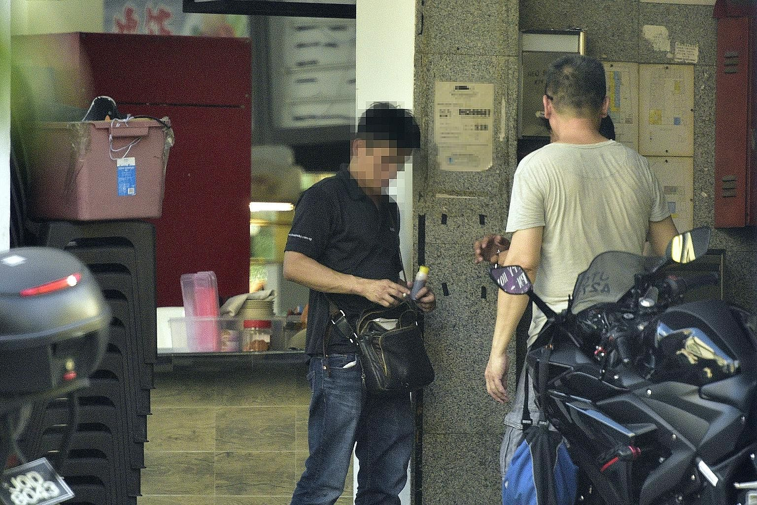 A buyer (in black) procuring a bottle of cough syrup behind a coffee shop in Geylang Lorong 7 while a minder (in grey) looks on. The bottles are hidden inside mailboxes and motorcycle top cases just a few metres away, and are retrieved once a sale is