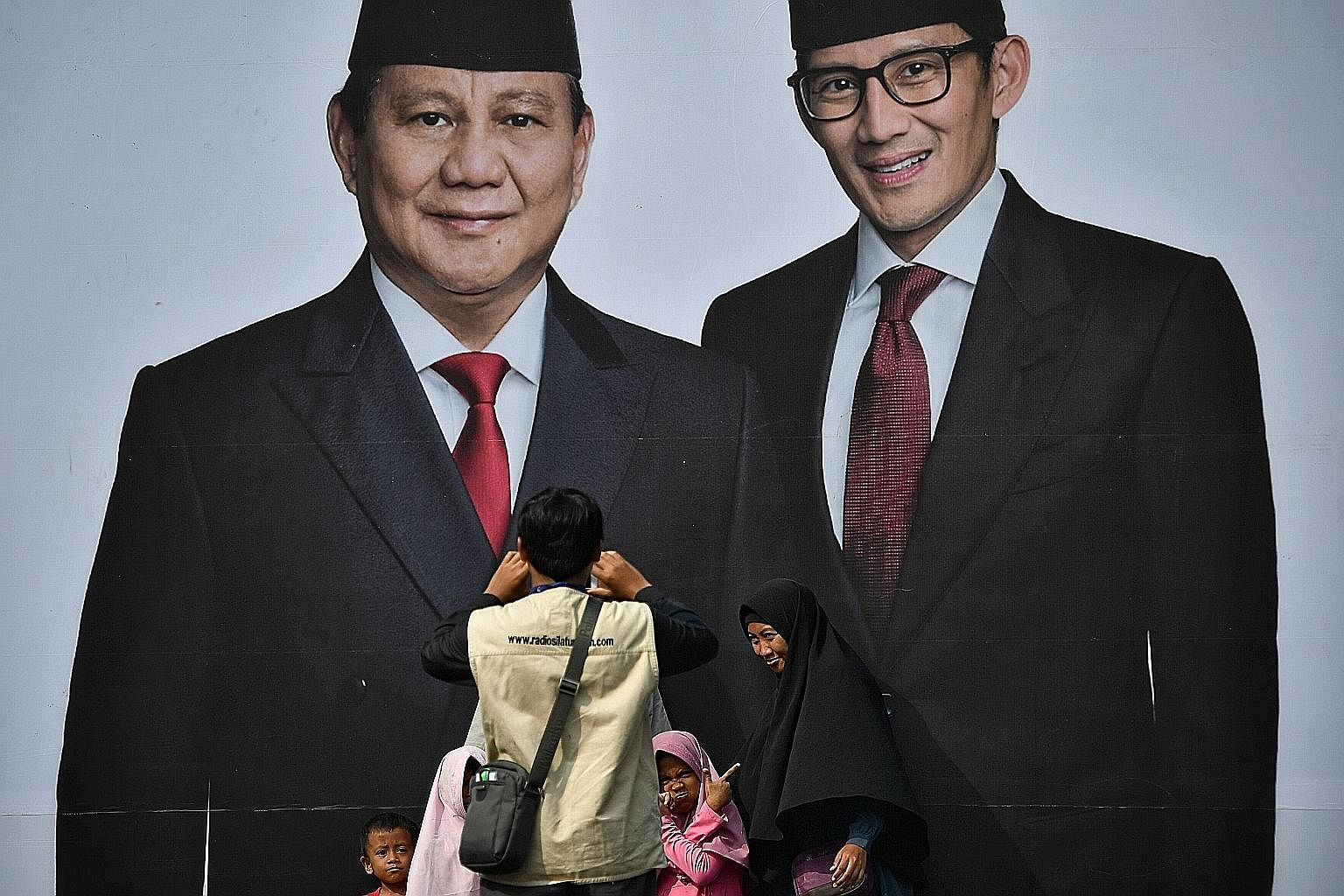 Supporters of presidential hopeful Prabowo Subianto taking pictures in front of a poster of him (left) and his running mate Sandiaga Uno at the Gelora Bung Karno Stadium yesterday, a day ahead of his mega rally there.