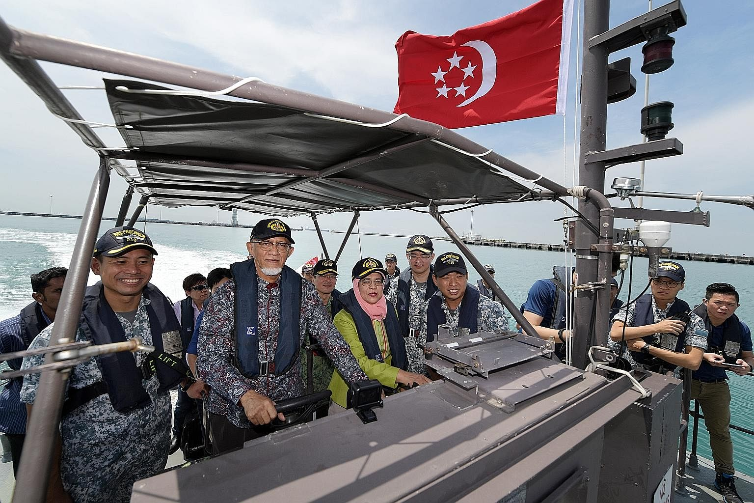 President Halimah Yacob and her husband Mohamed Abdullah Alhabshee (second from left) tried their hand at steering a Singapore navy fast craft at RSS Singapura-Changi Naval Base yesterday, with Military Expert 3 William Toh (right) guiding them. It w