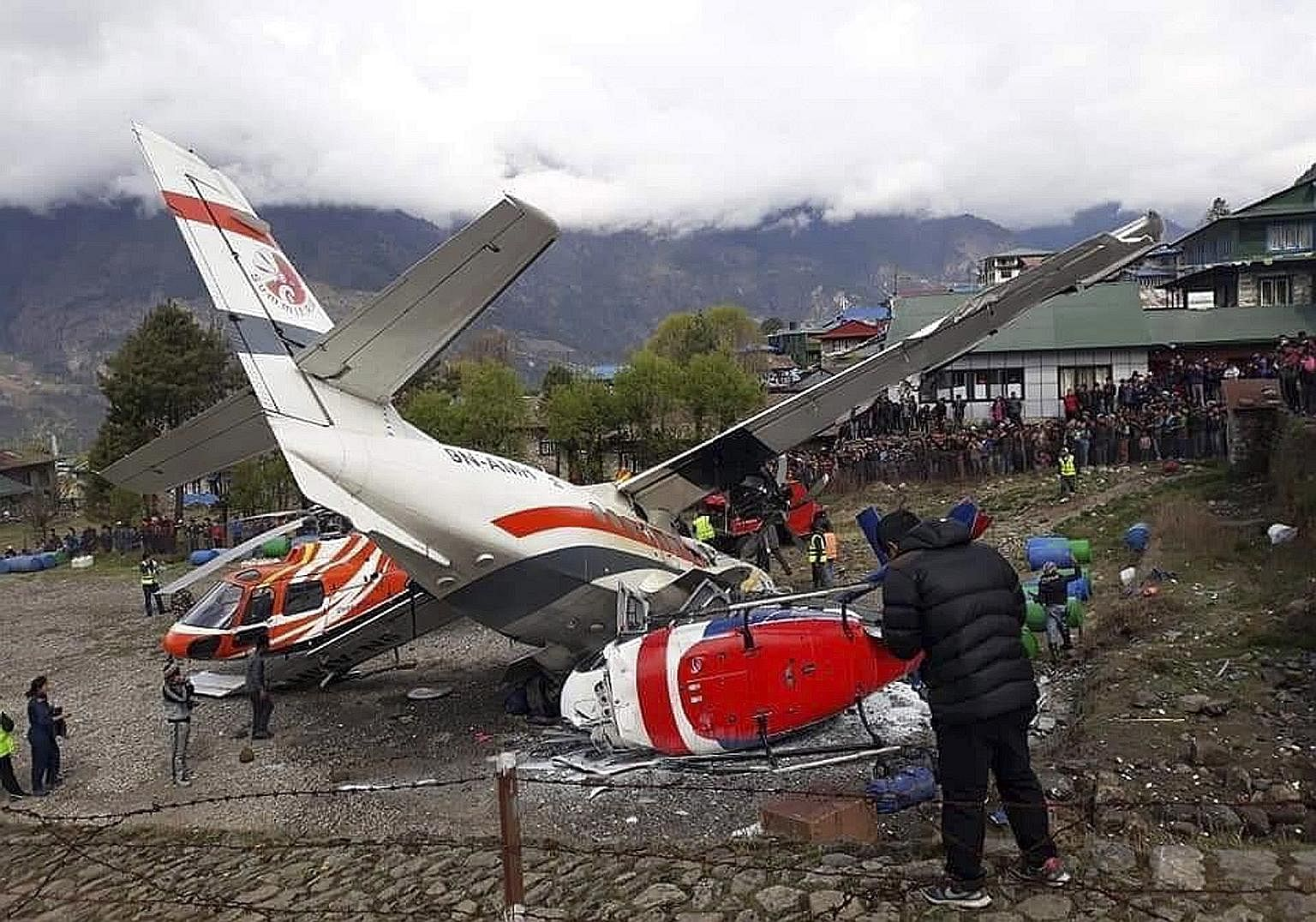 The wreckage of a Summit Air turbo-prop plane lying in between two helicopters on an airstrip at Nepal's Lukla Airport after the plane hit them during take-off yesterday. Three people - the plane's co-pilot and two police officers - were killed in th