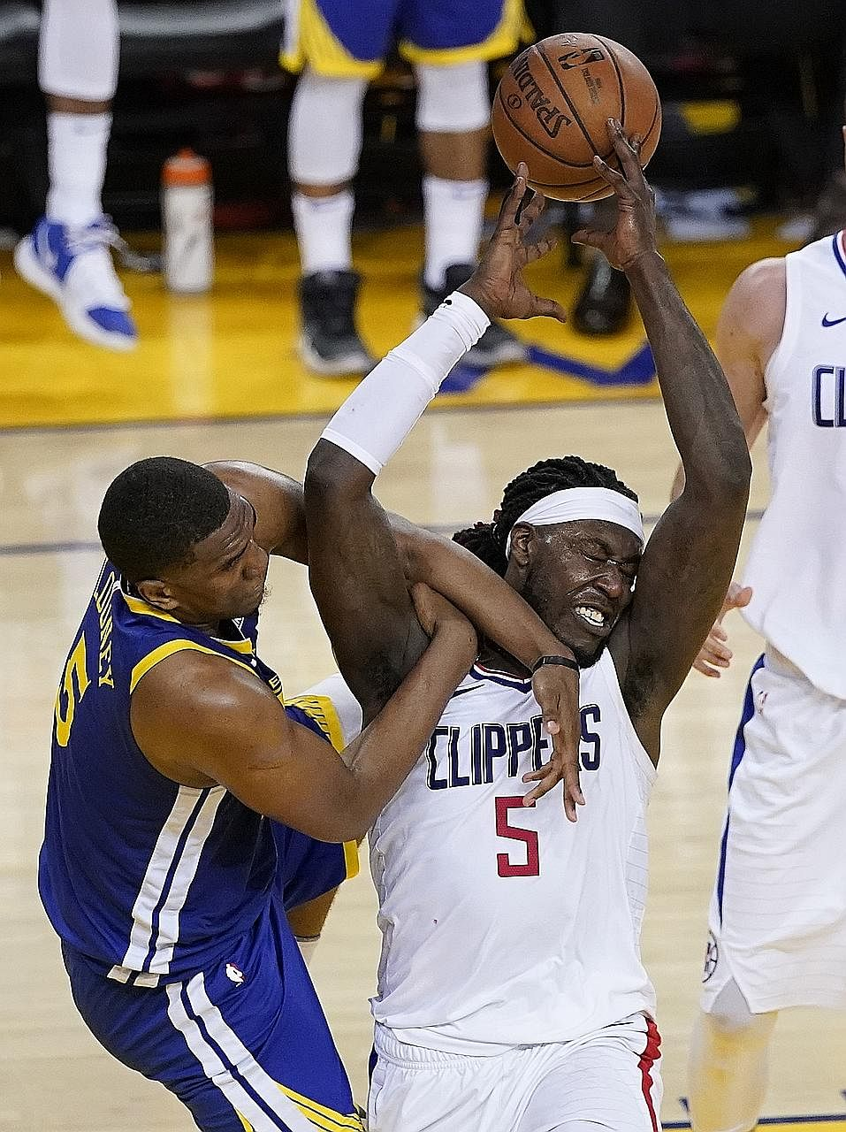Los Angeles Clippers forward Montrezl Harrell and Golden State Warriors centre Kevon Looney tussling for the ball during Game 5 of their NBA play-off first-round series. The Clippers won 129-121 to claw the series back to 3-2 and force Game 6 today i