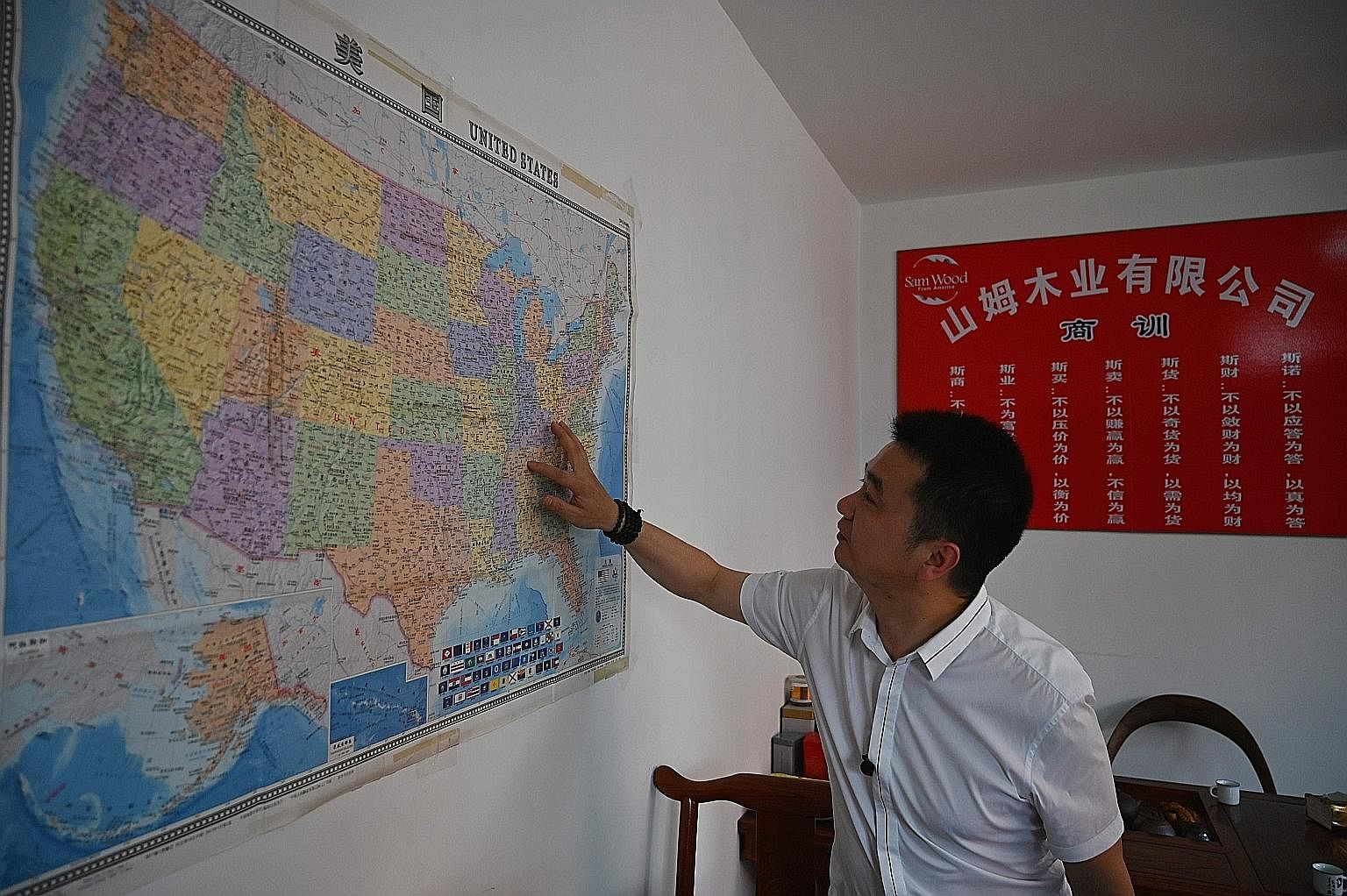 Mr Xu Xuebing, founder of China firm Sam Wood, showing where in the United States his company imports wood from. While China is ahead in some crucial areas, such as artificial intelligence, it is behind and dependent on foreign sources - especially t