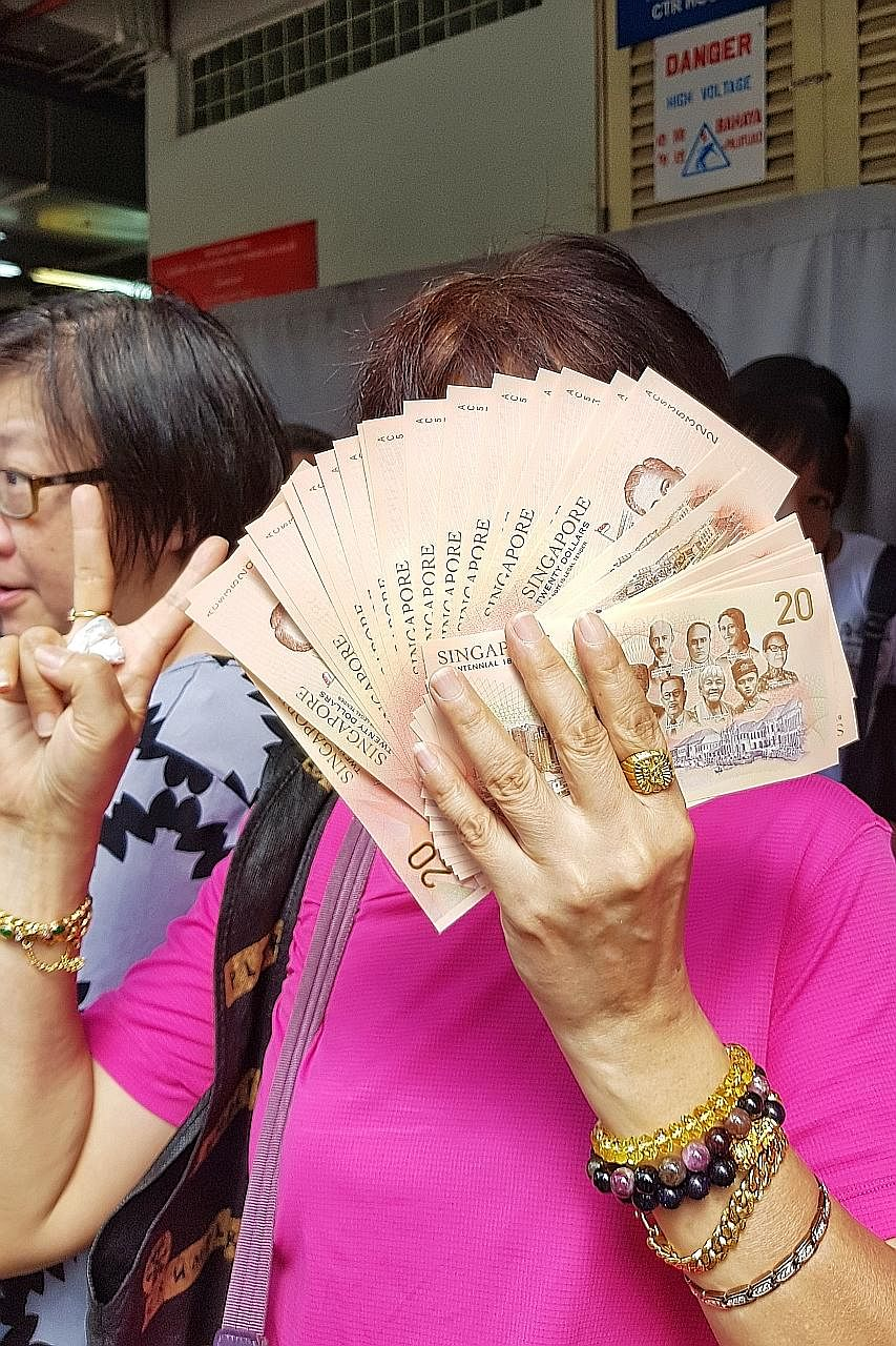 Each person is allowed to exchange for up to 20 pieces of the new $20 note in each transaction. Long queues were seen at many bank branches across the island, including the OCBC branch in Toa Payoh Central (above), from early yesterday morning.