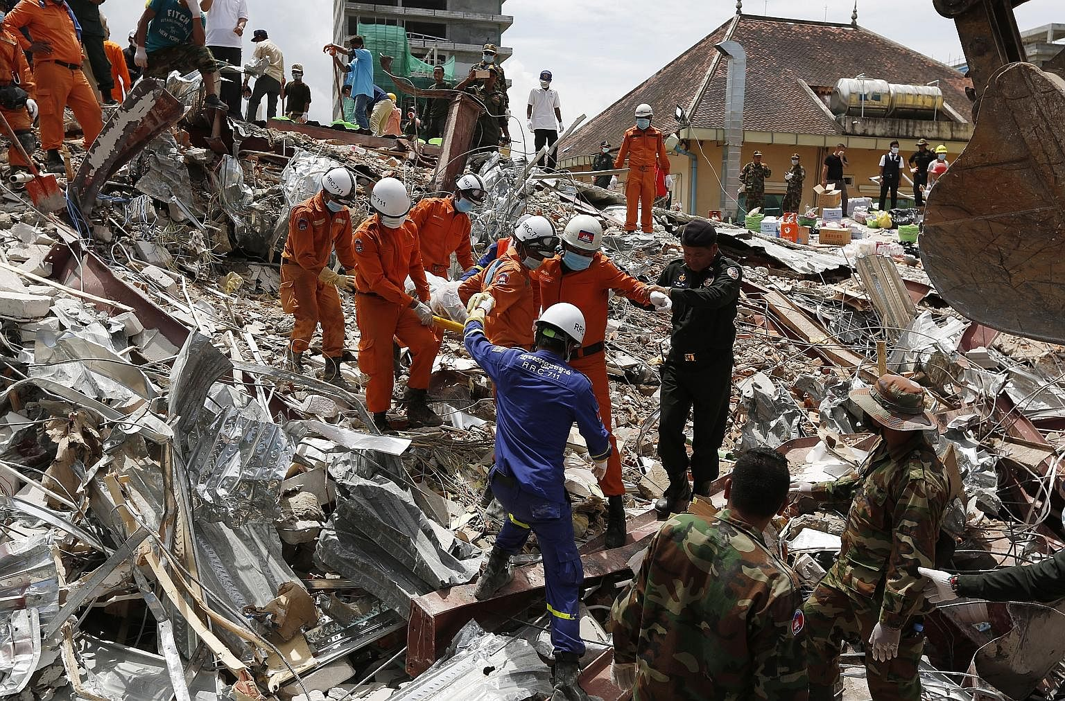 A Cambodian rescue team carrying the body of a worker who was killed at the site of a collapsed building in the coastal town of Sihanoukville. At least 1,000 rescue workers, soldiers, police, medics and Chinese construction experts have been deployed