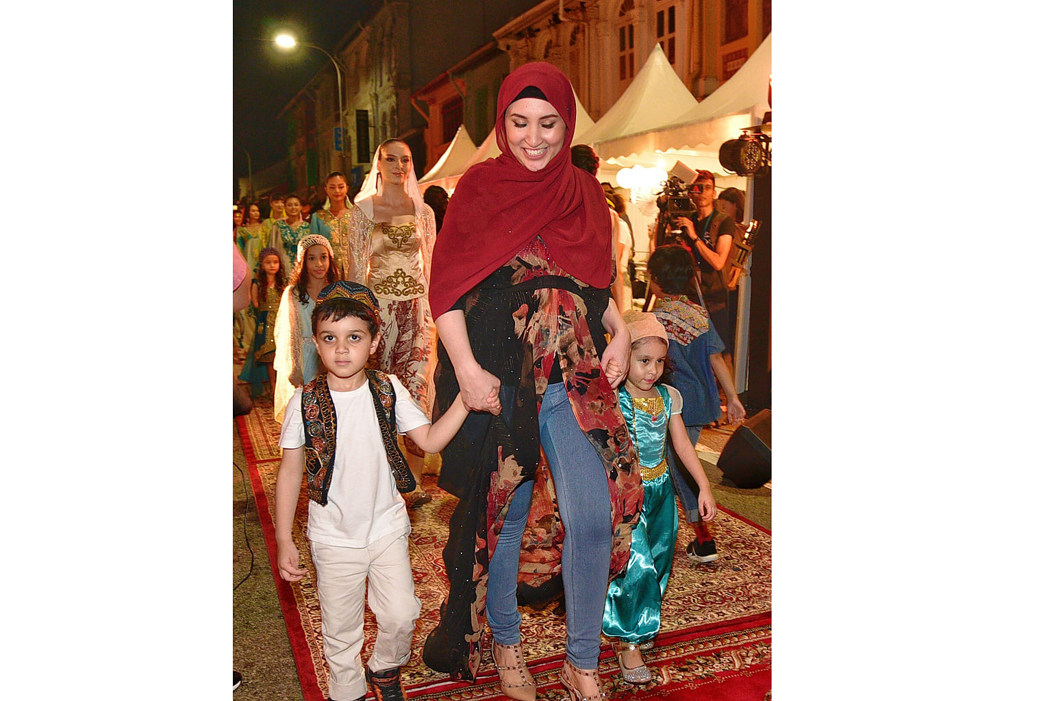 Models at the outdoor fashion show in Kampong Glam yesterday. The show featured designs inspired by the architectural features and history of the precinct, using textiles sourced from merchants in Arab Street. The event was part of the Great Singapore Sal