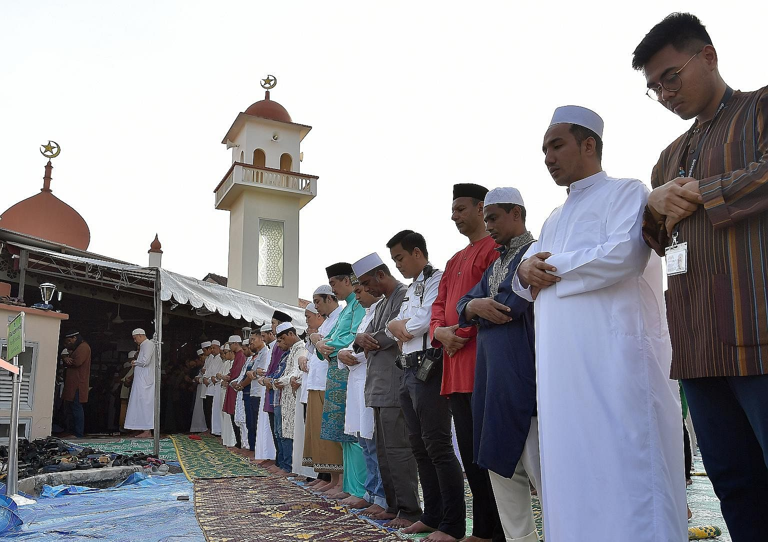 More than 1,000 Muslims gathered at the Abdul Razak Mosque yesterday morning, with many doing their Hari Raya Haji prayers on the road, along Jalan Ismail, off Jalan Eunos. To ensure that the mosque's volunteers could also join in the prayers, volunt