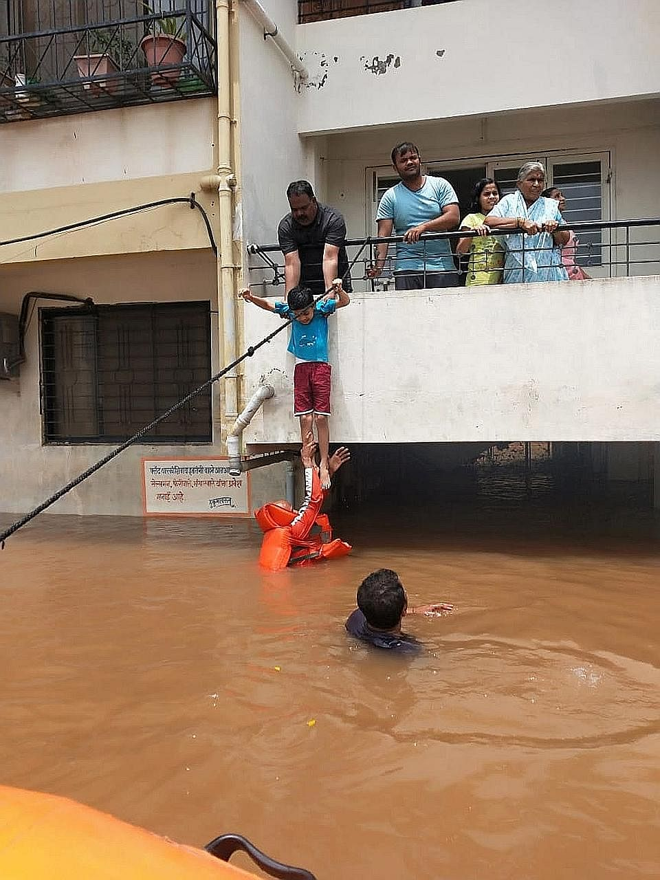 Members of India's National Disaster Response Force evacuating a child while other residents waited for their turn in the flood-hit area of Sangli in Maharashtra state on Sunday.