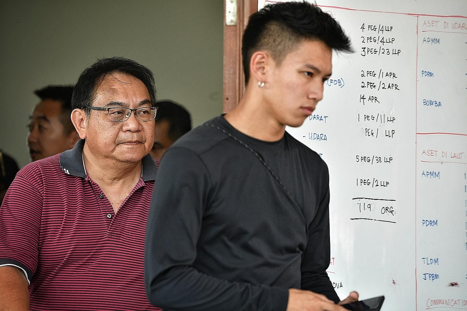 Mr Peng Mun Kit, husband of missing kayaker Puah Geok Tin, and his younger son Louis after they were told by Malaysian officials in Mersing yesterday afternoon that an unidentified body - believed to be that of Madam Puah - had been found in the wate