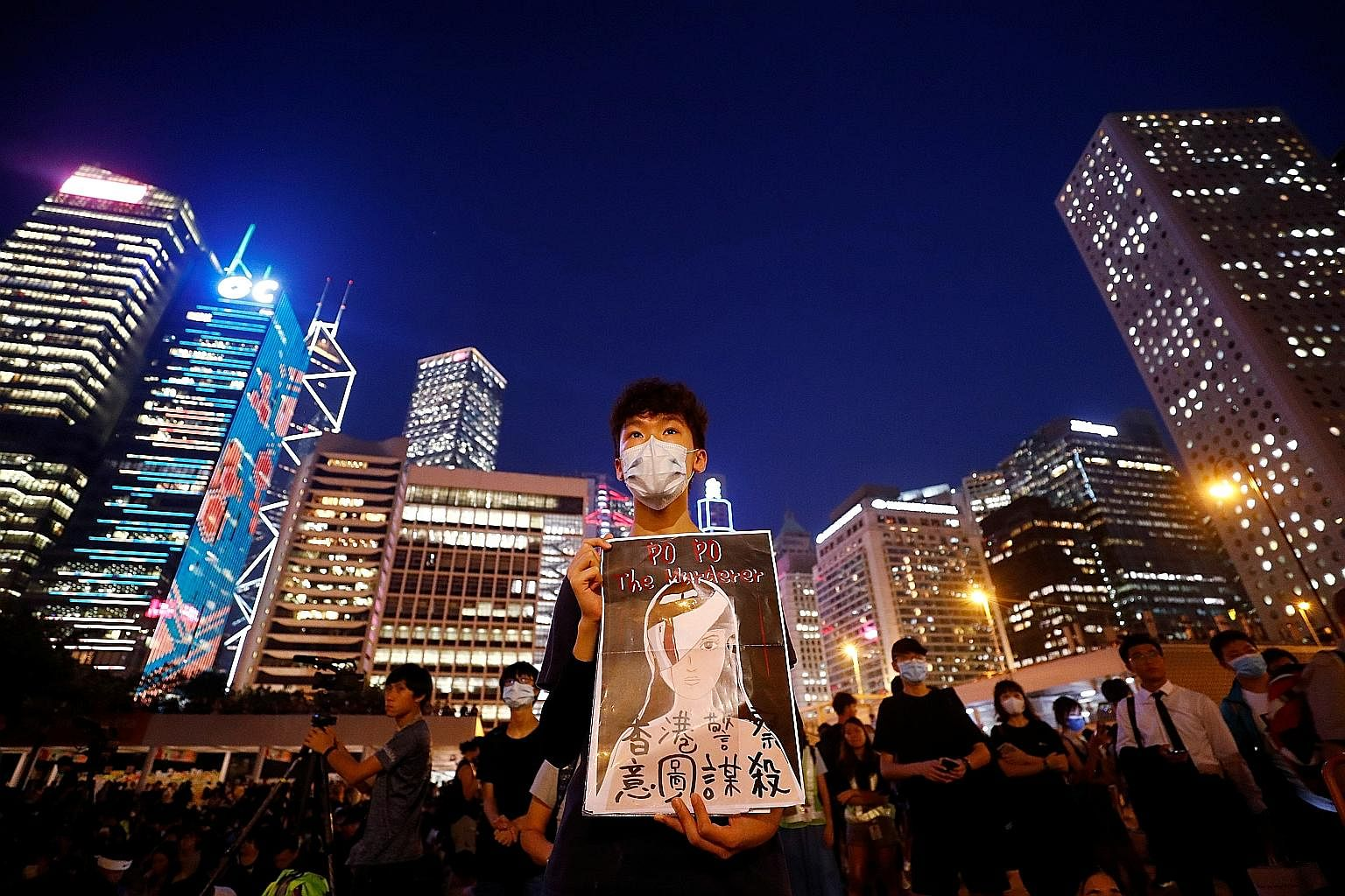 A student holding a poster depicting a female protester whose eye was injured, at a rally calling for political reforms outside City Hall in Hong Kong yesterday. Some felt it was unjust that only two people in the Yuen Long attack have been charged s
