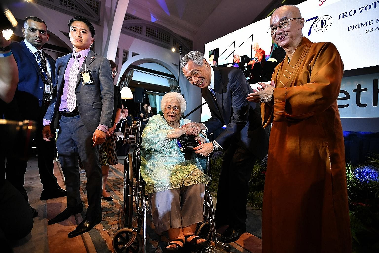 Prime Minister Lee Hsien Loong presenting an award yesterday to Mrs S R Nathan for her husband, the late president S R Nathan, for his efforts in promoting religious harmony. With him was Venerable Kwang Phing (far right), president of Singapore's In