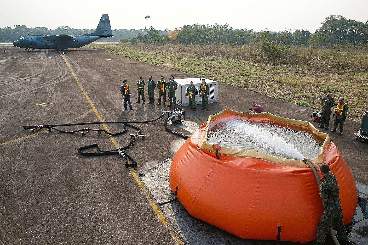 A Hercules C-130 aircraft of the Brazilian Air Force waiting to collect giant water bags to fight fires in the Amazon rainforest, in the state of Rondonia, one of the states most affected by the wildfire crisis. About 60 per cent of the Amazon is in