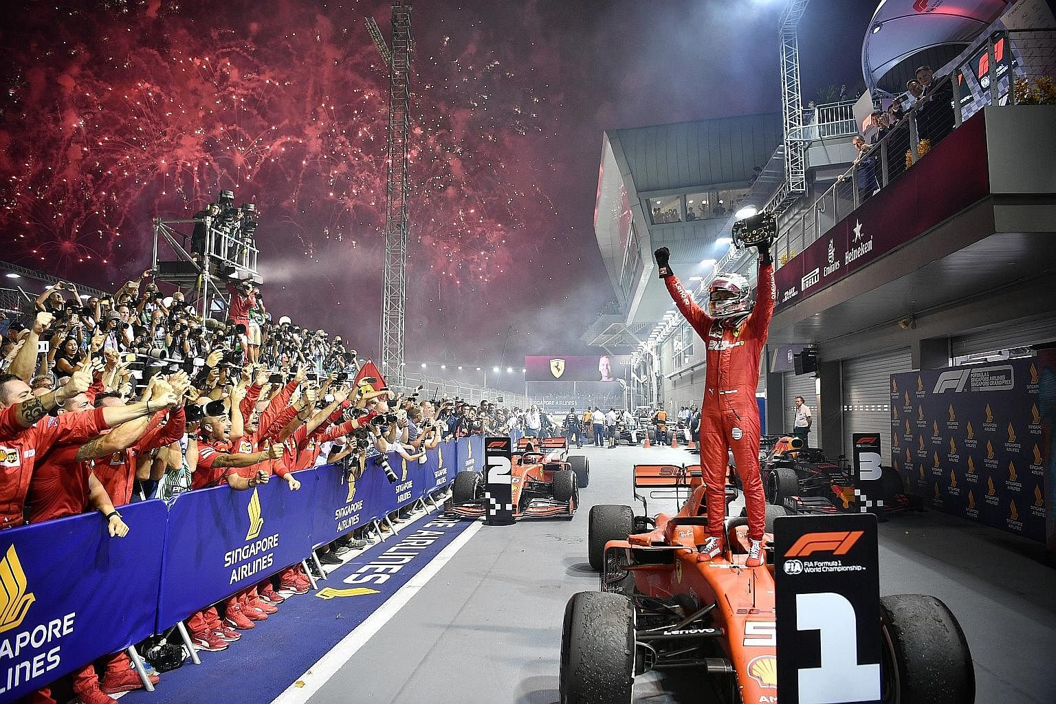 Ferrari's Sebastian Vettel celebrates after winning a record fifth title at the Singapore Airlines Singapore Grand Prix last night. The German four-time world champion started the 61-lap race in third place, before clinching top spot for his first ra