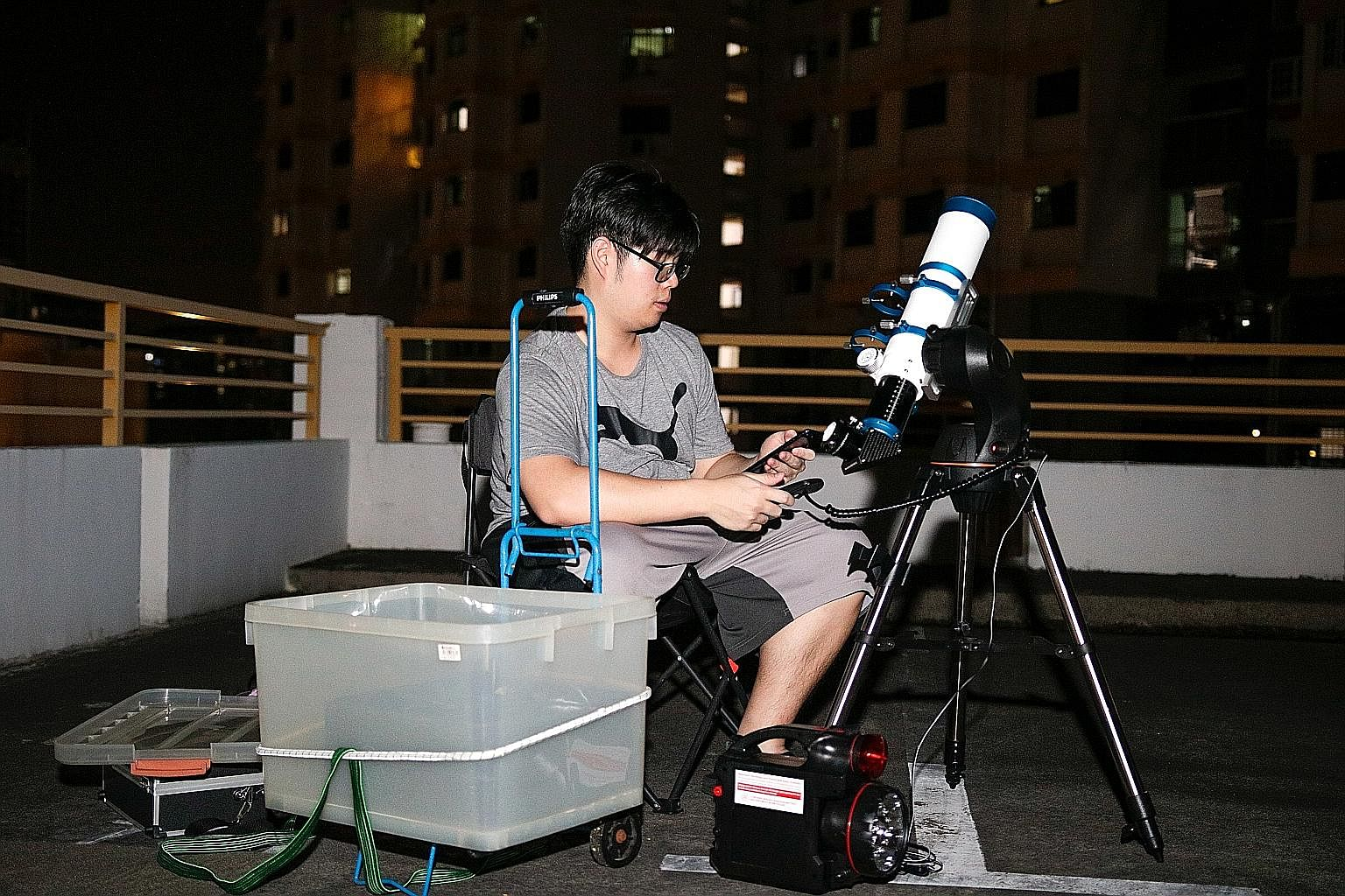 Mr Ethan Chong looking through his telescope on a clear night. Mr Chong has two telescopes - an Orion and a William Optics - for which he paid $1,600 in total. He fell in love with astronomy after a trip to Bintan with Nanyang Polytechnic's astronomy