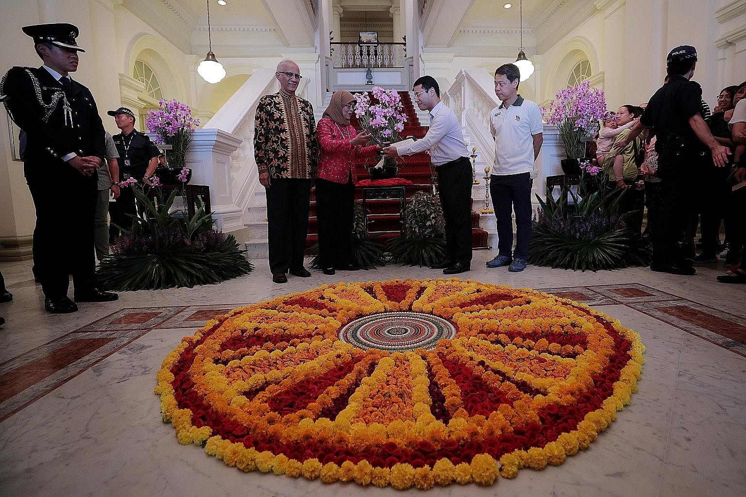 President Halimah Yacob unveiling the new Bicentennial Orchid at the Istana yesterday with Second Minister for National Development Desmond Lee, who is also Minister for Social and Family Development. They are flanked by Madam Halimah's husband, Mr M