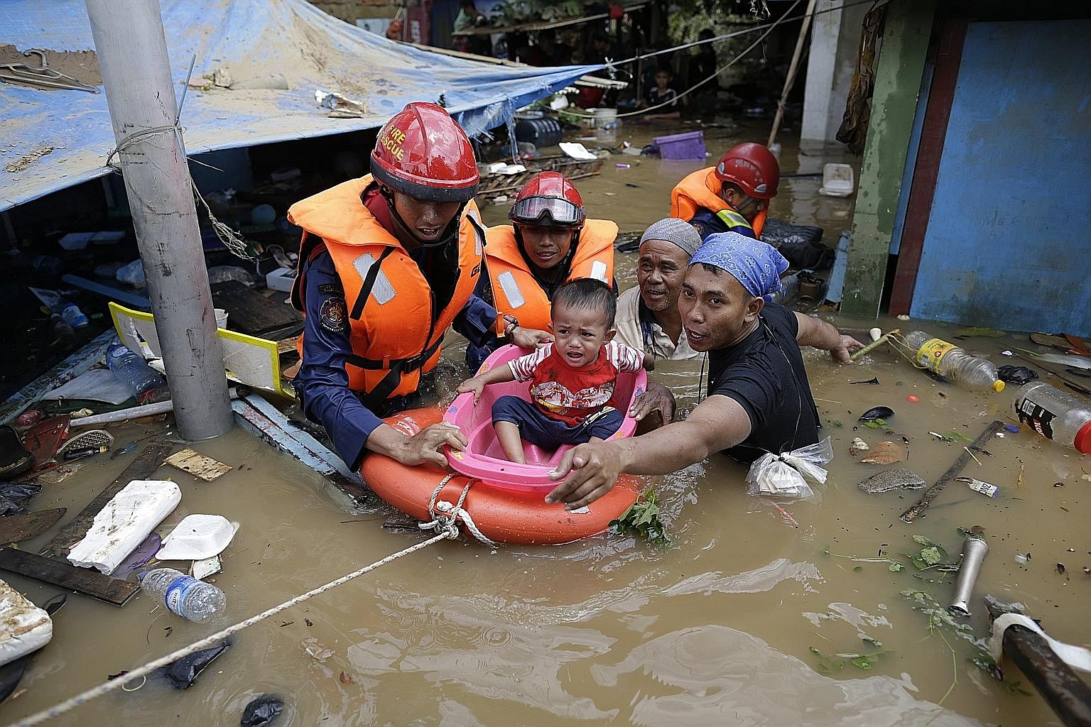 Indonesian rescuers evacuating a boy from a flooded area in Jakarta yesterday. Severe flooding and landslides caused by torrential rain over the New Year period have killed at least 26 people and left thousands more in the Indonesian capital and its
