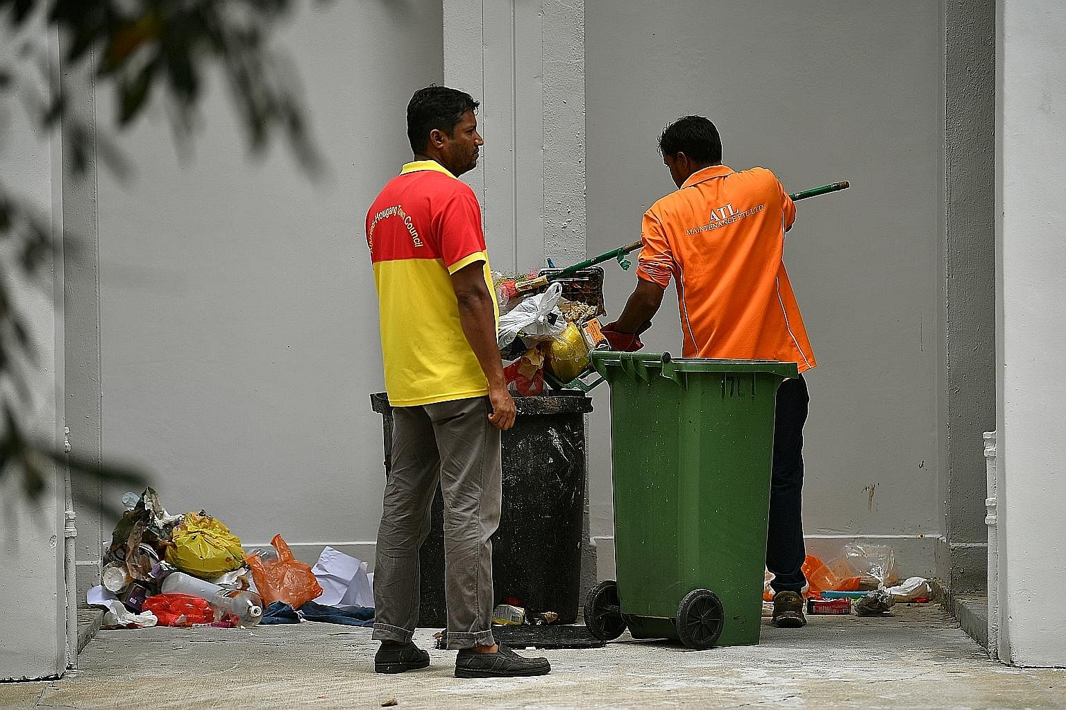 Cleaners putting back the contents of a rubbish chute bin at Block 534 Bedok North Street 3 after it had been checked by investigators.