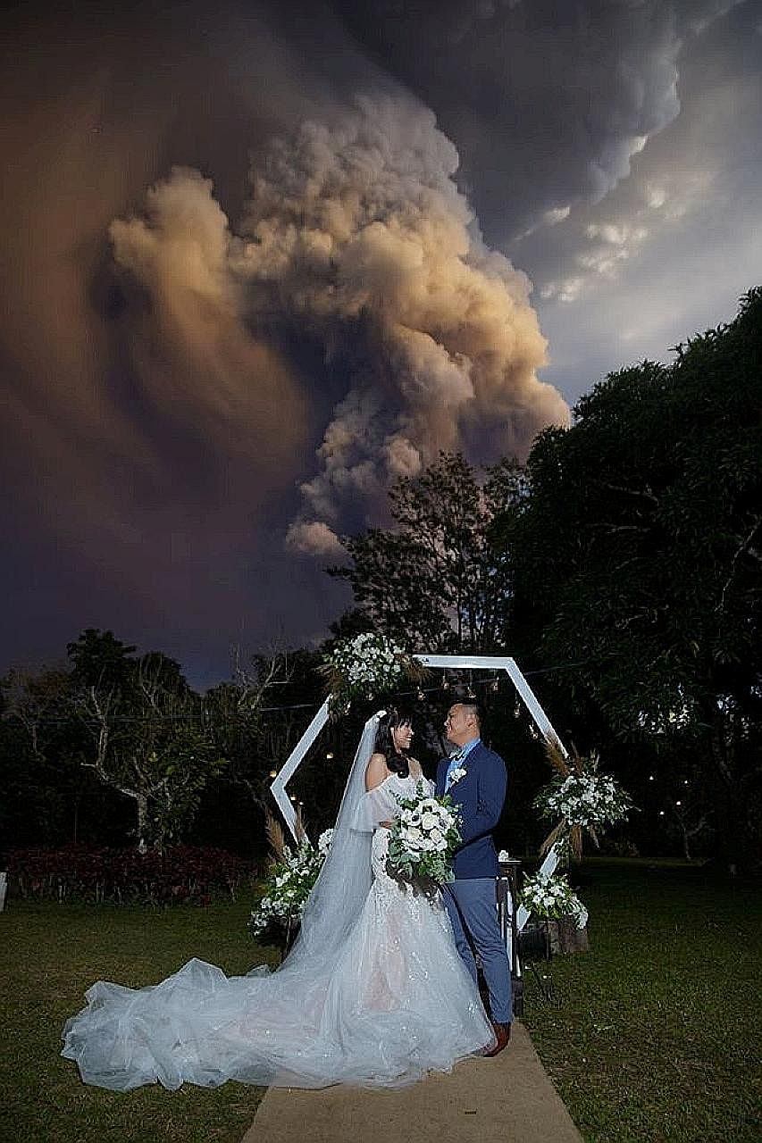 Filipinos Chino and Kat Palomar exchanged vows in Cavite province on Sunday under a huge cloud of smoke and ash from Taal.