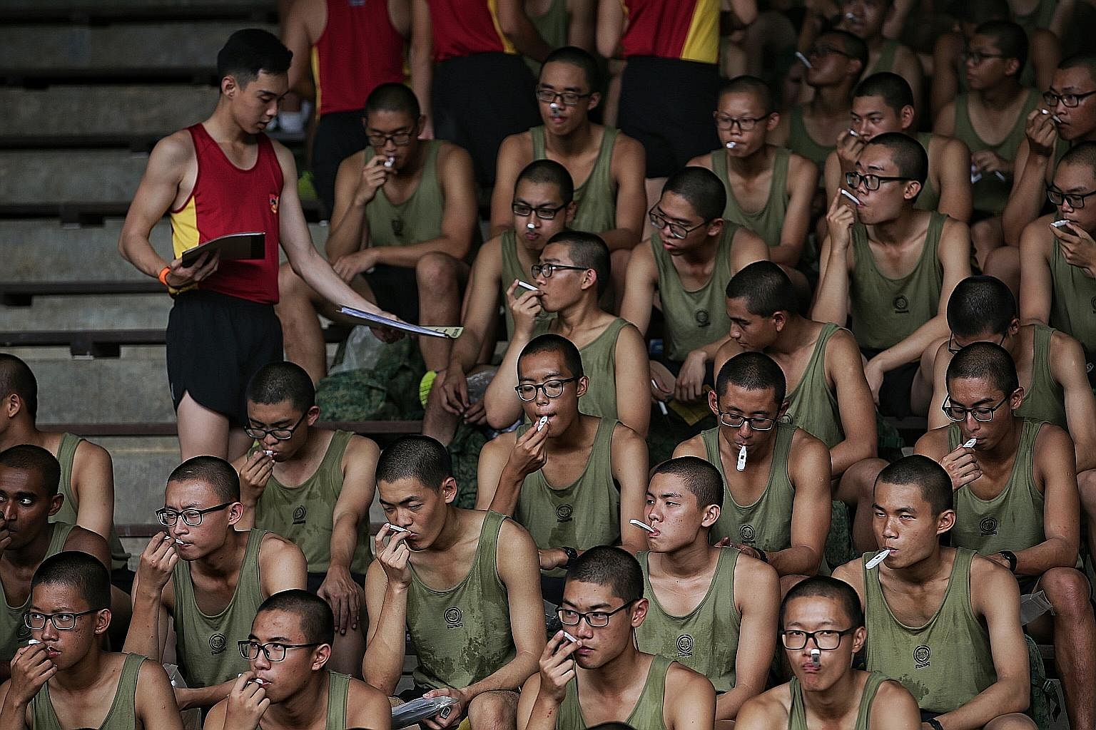Army recruits taking their temperature yesterday at the Basic Military Training Centre on Pulau Tekong. The Singapore Armed Forces has put in place new measures to prevent the spread of the coronavirus, but currently has no plans to cancel in-camp tr