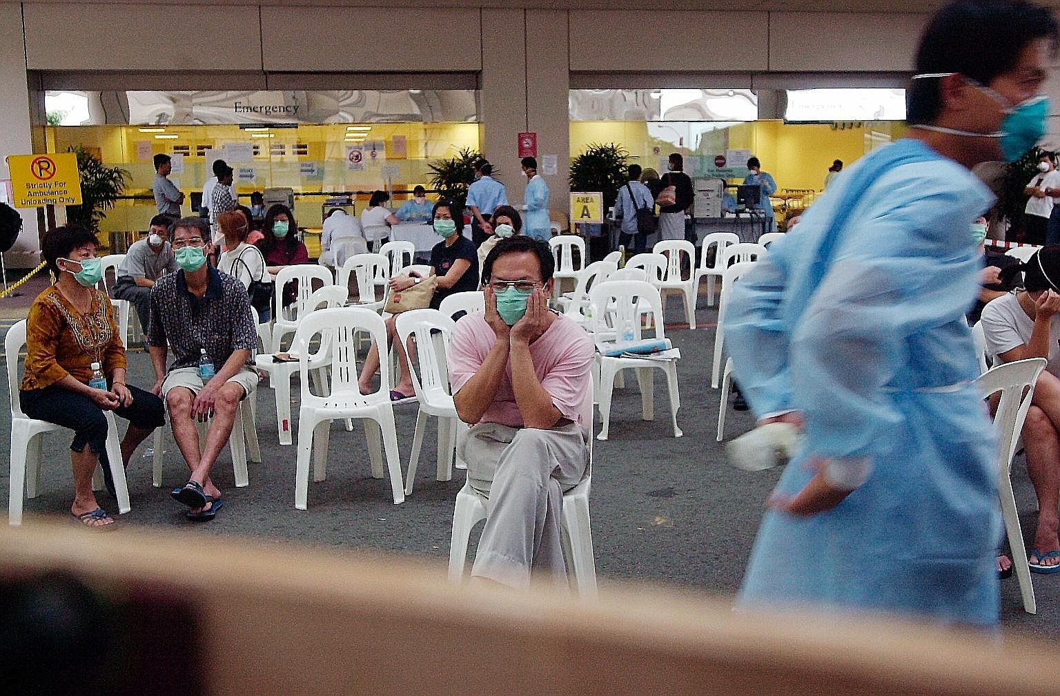 Patients waiting to be screened for the severe acute respiratory syndrome outside Tan Tock Seng Hospital's accident and emergency department during the outbreak. The writer points out that during the Sars crisis in 2003, the people of Singapore behav