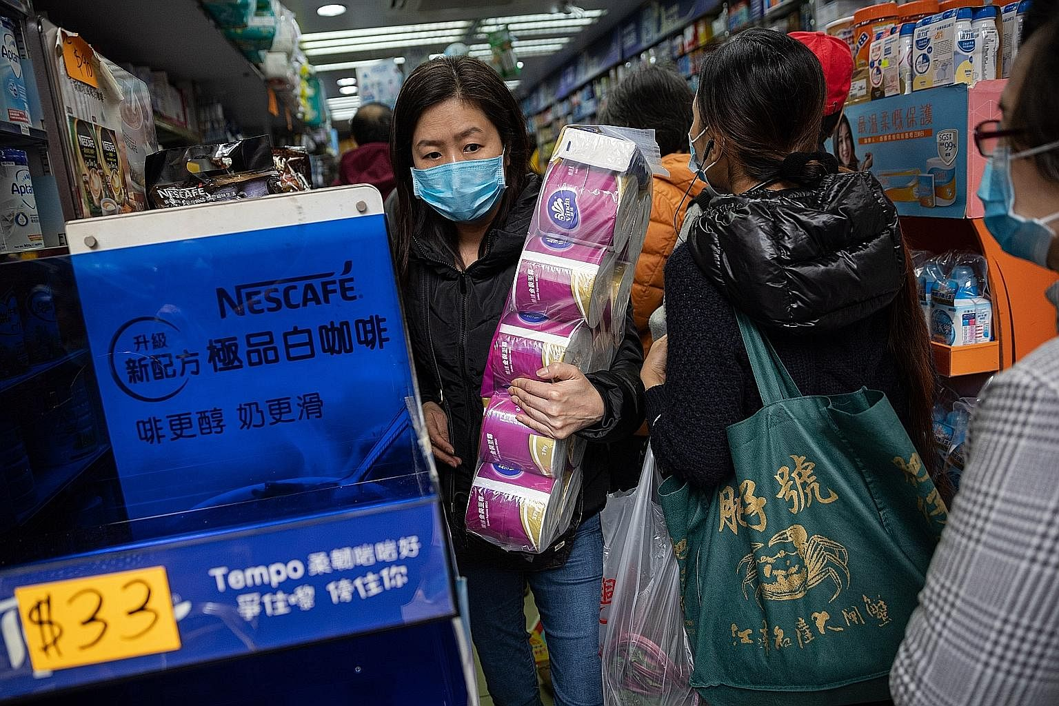 A shopper stocking up on toilet paper at a drugstore in Hong Kong. Threats that feel out of control, like a runaway illness outbreak, lead people to seek ways to re-impose control, for instance by hoarding supplies.