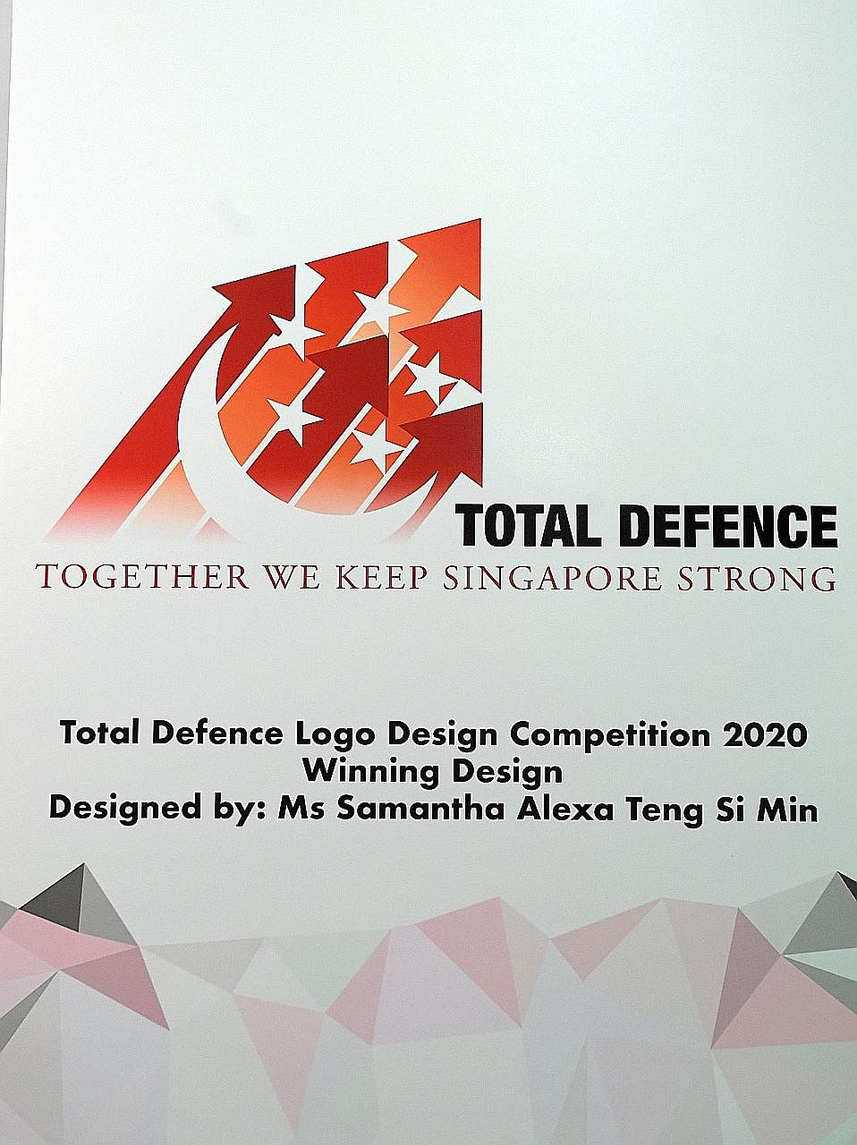 Minister for Trade and Industry Chan Chun Sing chatting with Ms Samantha Alexa Teng (right), the winner of the Total Defence Logo Design Competition 2020 (below). Beside him is Colonel Jerica Goh, director of Nexus, the Ministry of Defence's central