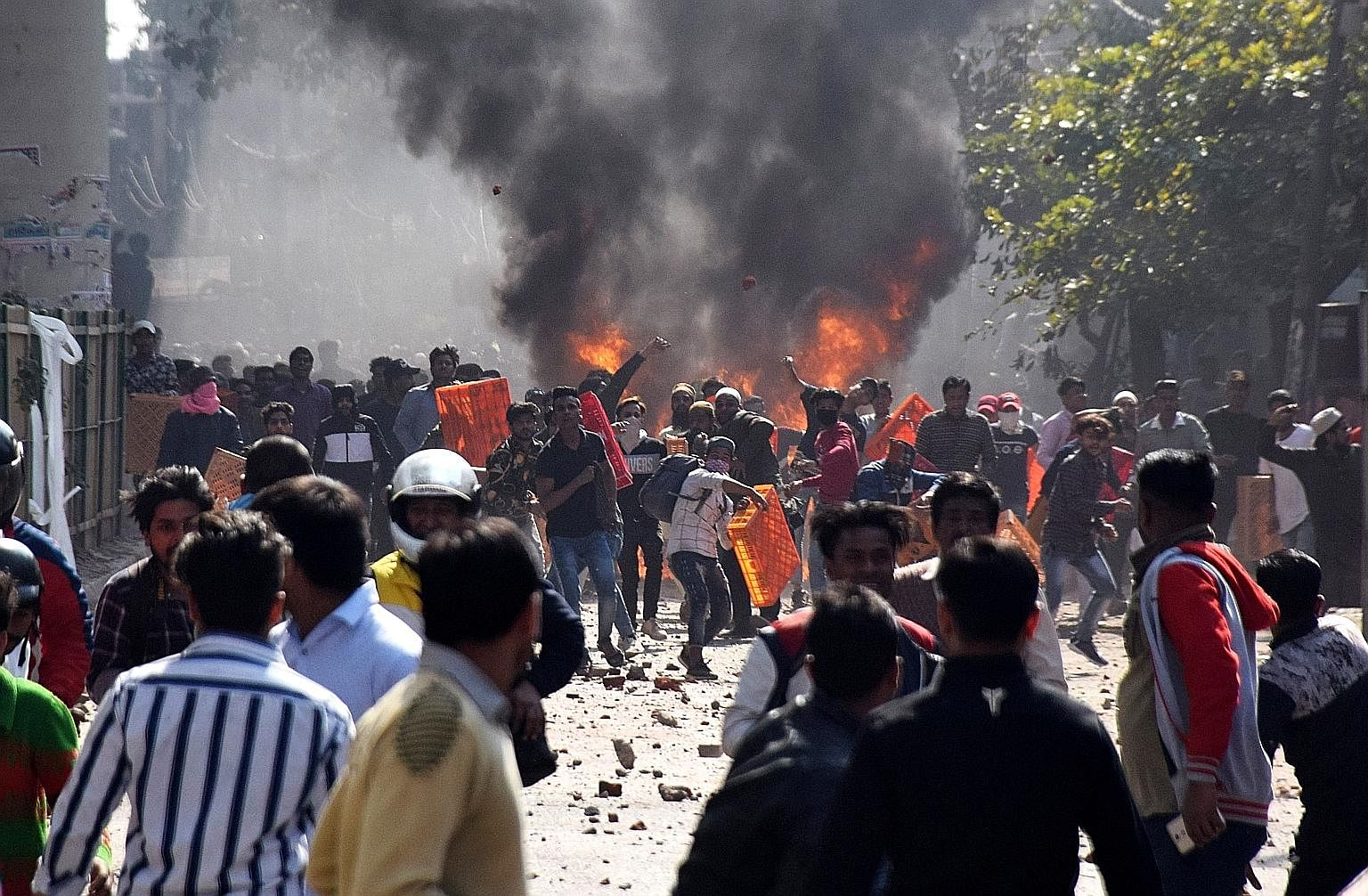 Men pelting stones and starting fires during clashes in eastern Delhi between groups for and against India's Citizenship Amendment Act.