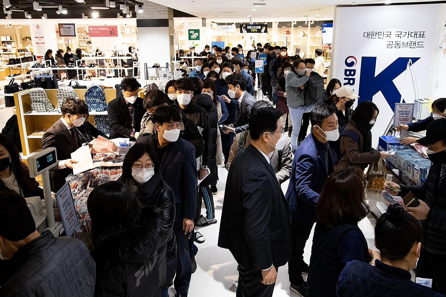 People queueing to buy masks supplied by the government at a department store in the Mokdong district of Seoul yesterday. Workers in protective suits spraying disinfectant on a store window in Munjeong-dong Rodeo Street in the Songpa district of Seou