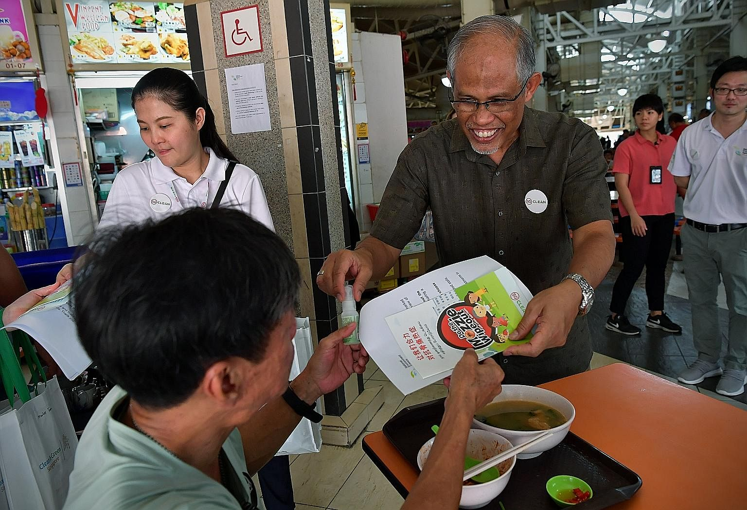 Environment and Water Resources Minister Masagos Zulkifli giving out mosquito repellents and information booklets at the launch of the National Dengue Prevention Campaign in Ang Mo Kio yesterday.