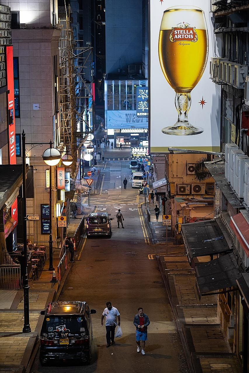 With bars and restaurants in Hong Kong being asked to stop selling alcohol in a bid to curb the spread of the coronavirus, the usually packed Lan Kwai Fong bar district has seen shuttered units (far left) and near-empty streets (left) this week. PHOT