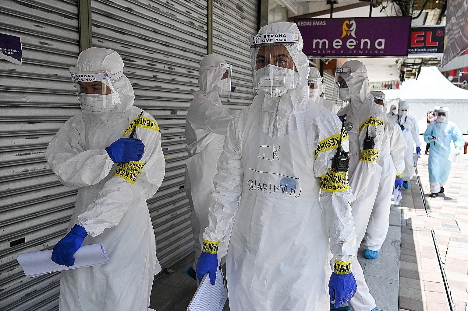 Health workers on their way to two apartment buildings in Kuala Lumpur last Wednesday, after they were cordoned off following several Covid-19 infections. Most Asean countries have tightened border controls, issued lockdown orders or taken social dis