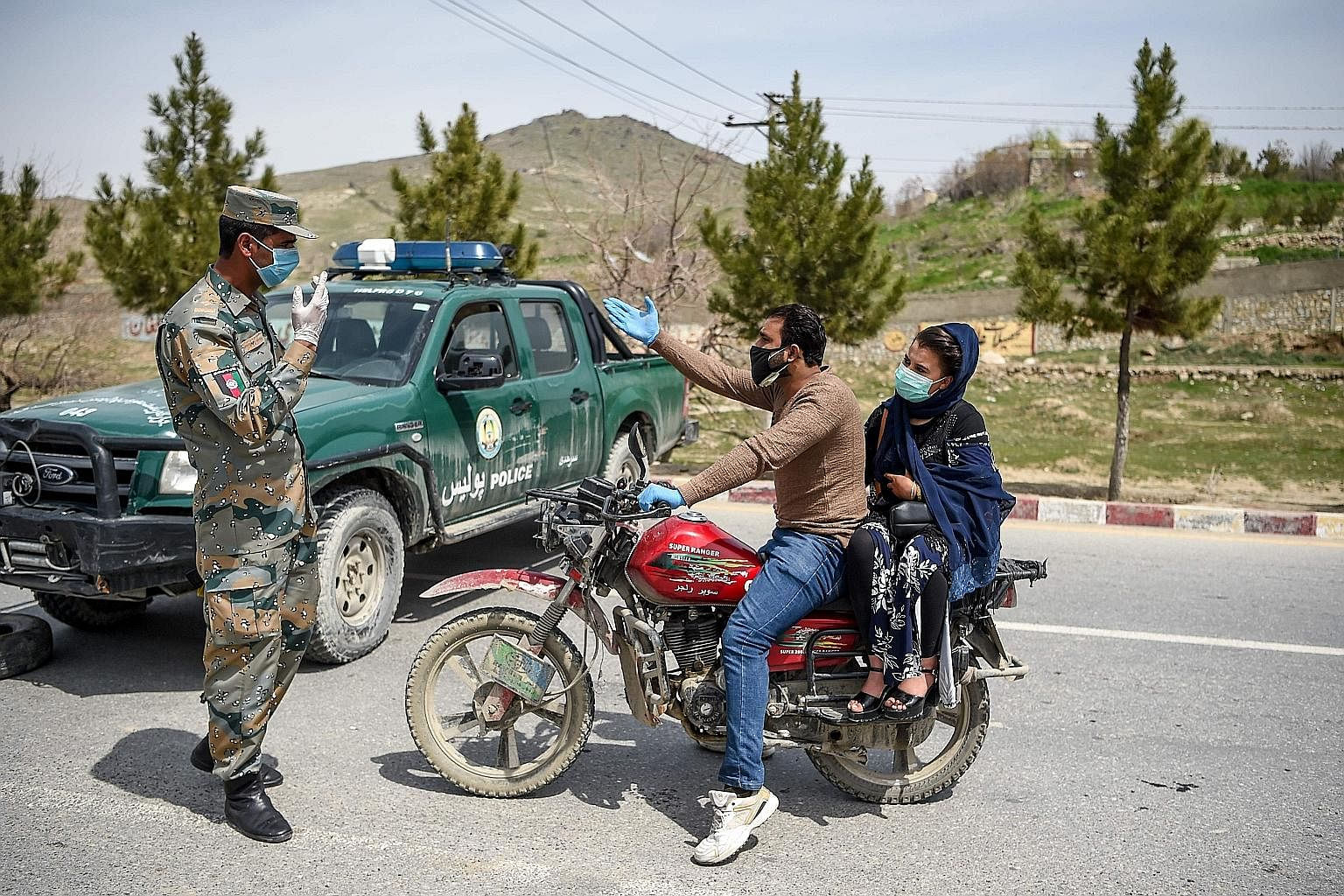 An Afghan security officer stopping motorists at a checkpoint in Kabul on April 8, during a government-imposed lockdown as a preventive measure against Covid-19. The virus may have brought much of the world to a standstill, but it has not ended confl