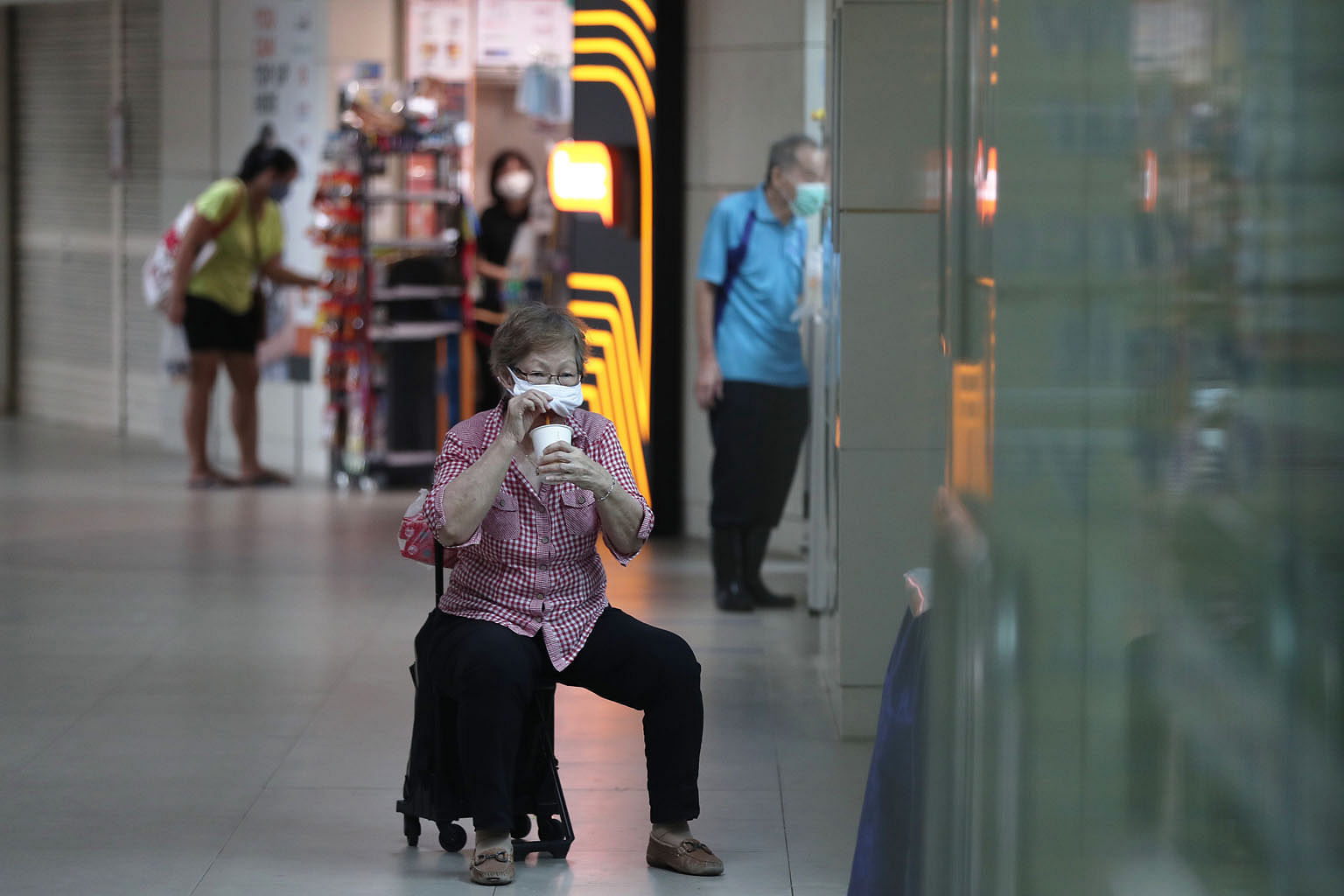 A woman resting on her trolley chair at Clementi bus interchange last Thursday. Tighter restrictions on the movement and gathering of people have thinned out crowds at public places.