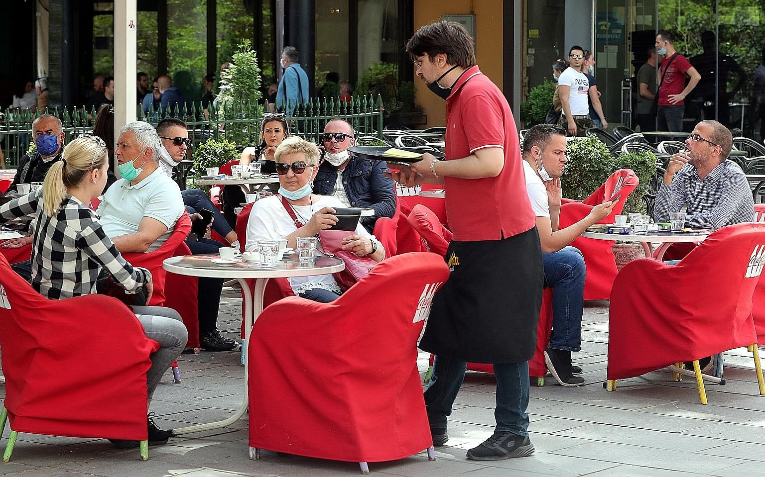The crowd, mostly wearing face masks, at an outdoor cafe in Sarajevo, Bosnia and Herzegovina, last Wednesday. Restaurants and hotels are reopening in the West Balkan country after remaining closed for the past two months due to the on