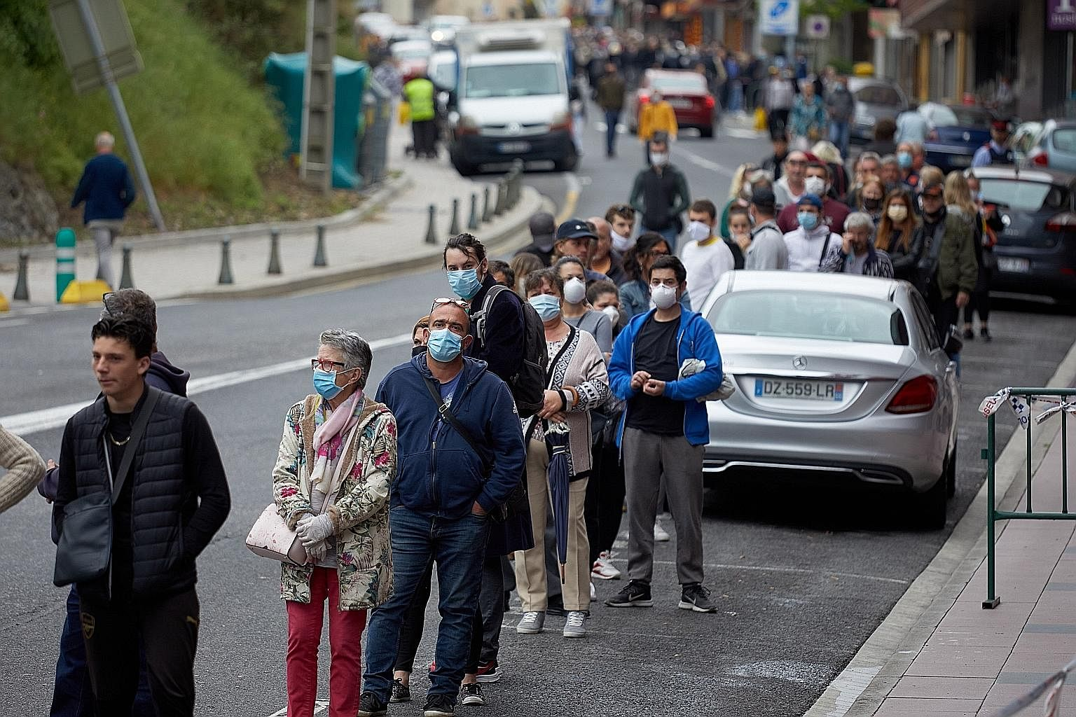 A long queue outside a shop in the Spanish border town of El Pertus last Tuesday. As restrictions eased, people living on the French-Spanish border have been crossing over to Spain to buy items such as cigarettes and alcohol, which a