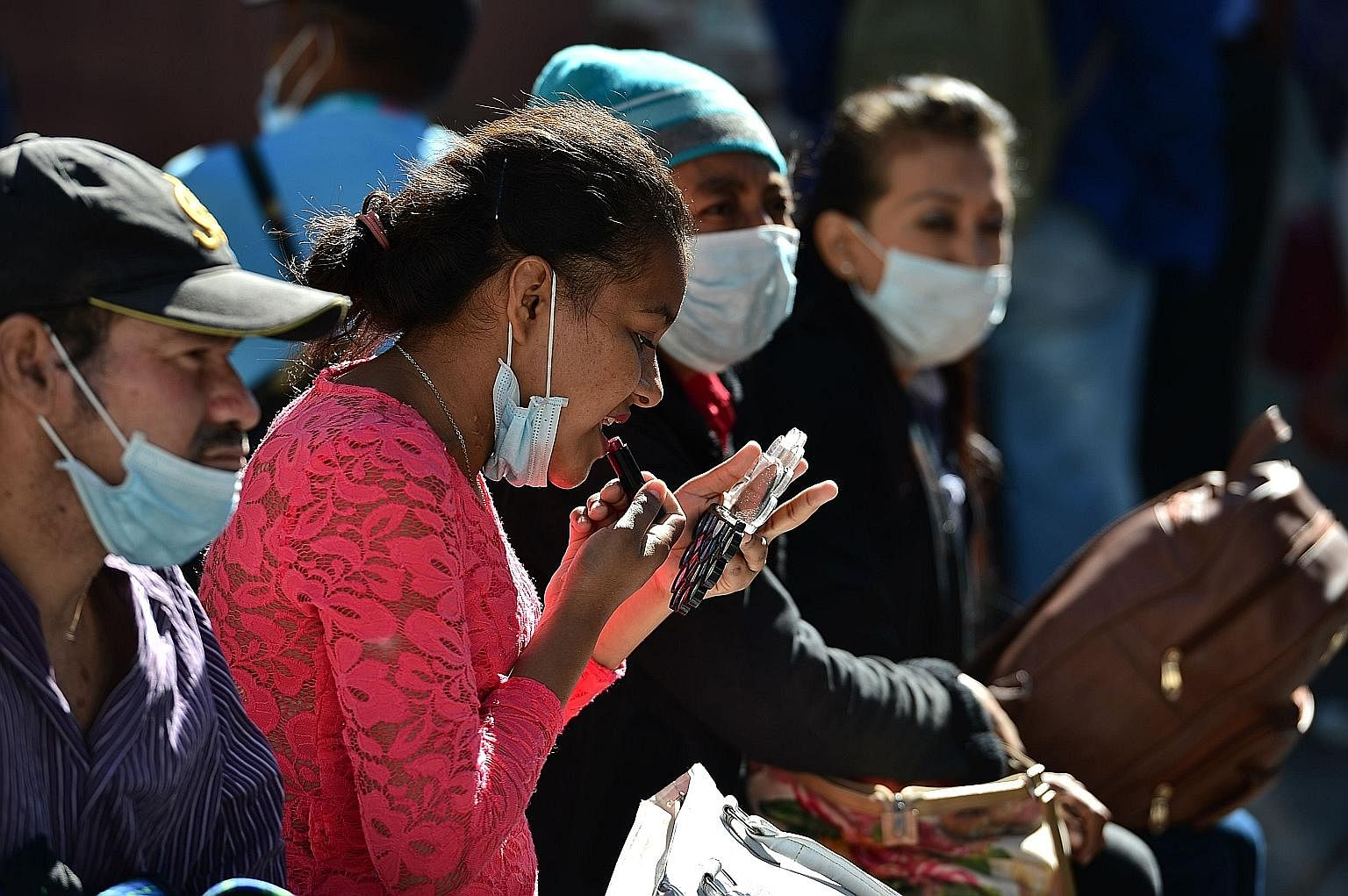 A woman applying lipstick next to people wearing face masks amid the coronavirus outbreak, in Tegucigalpa, Honduras, in March. With face coverings an inevitable part of our essential attire for some time to come at least, some are wondering about the