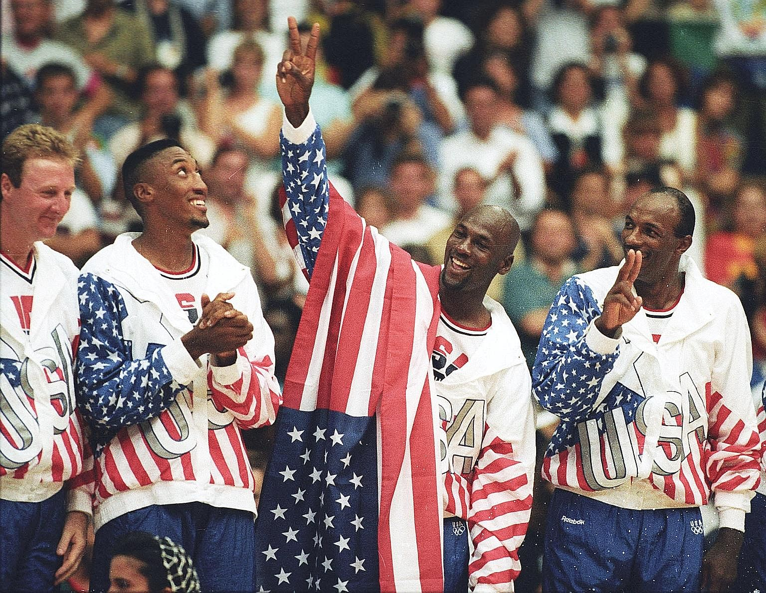 American basketball player Michael Jordan (draped with flag) flashes a victory sign as he stands with teammates (from left) Larry Bird, Scottie Pippen and Clyde Drexler. They were nicknamed the Dream Team after winning the Olympic gold in Barcelona, Spain