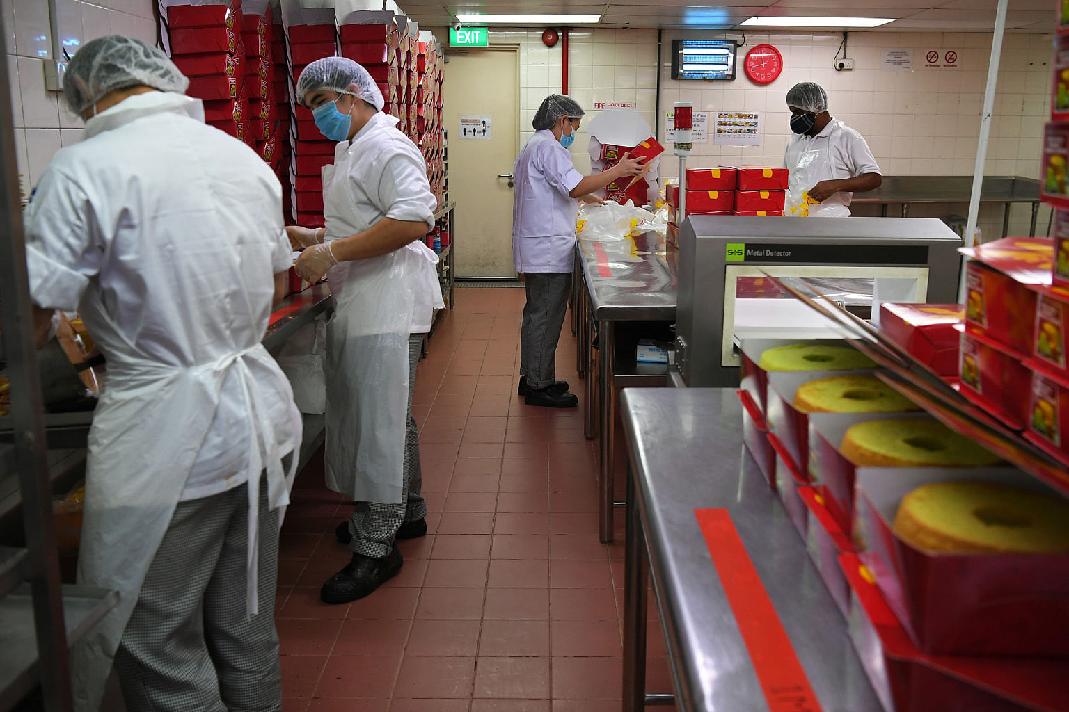 At Shine Precision Engineering in Pioneer, yellow boxes have been marked out next to the large machines to ensure that sufficient distance is kept between employees on the production floor. Cake decorators in confectionery chain Prima Deli's p