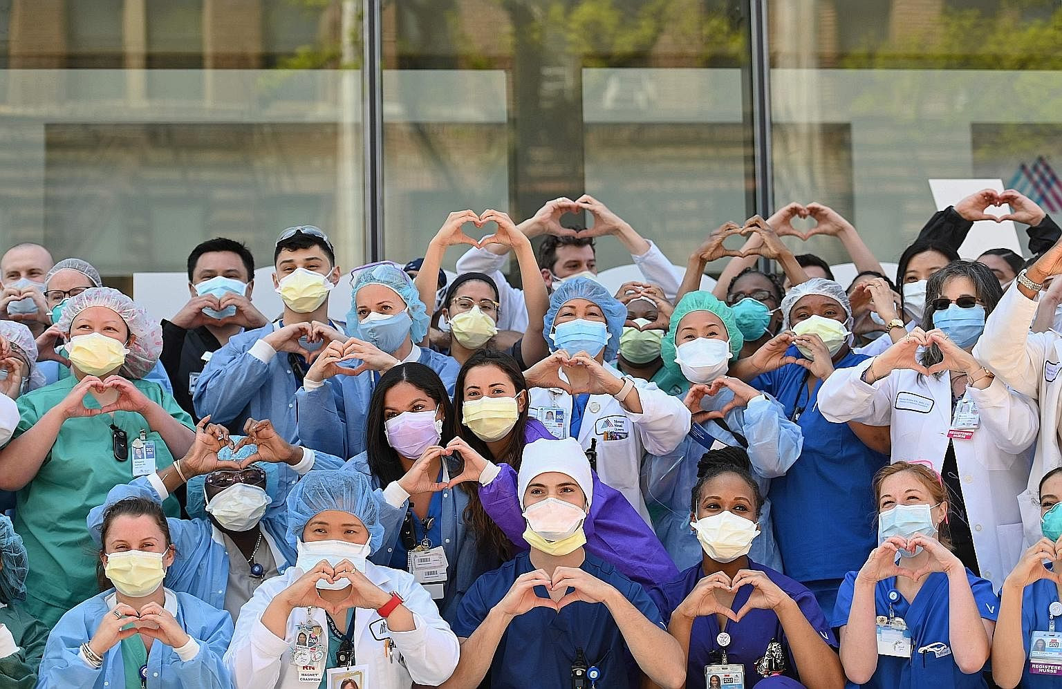 Nurses and healthcare workers gesturing love in celebration of Nurse Week and International Nurses Day outside Mt Sinai Queens in the Queens borough of New York City last Tuesday. ProPublica reported that at least 30 Filipino health workers had died