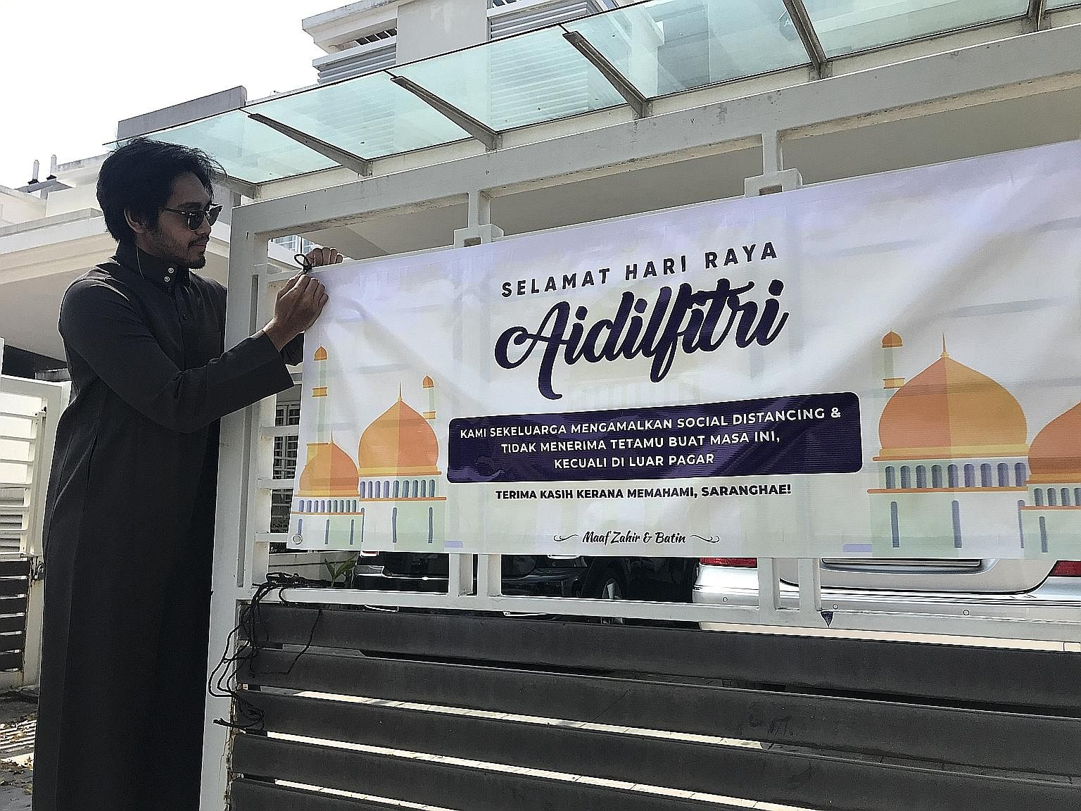 Mr Ahmad Afif Zainol putting up a Hari Raya banner outside his home in Alam Impian, Selangor. It comes with the message that the family is not accepting visitors amid the coronavirus pandemic.