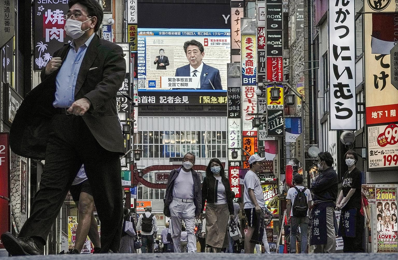 Japanese Prime Minister Shinzo Abe announced the end of a nationwide state of emergency in a live TV broadcast yesterday - seen here in Tokyo's Shinjuku area - as the number of coronavirus cases tailed off. He also announced plans for a second aid pa