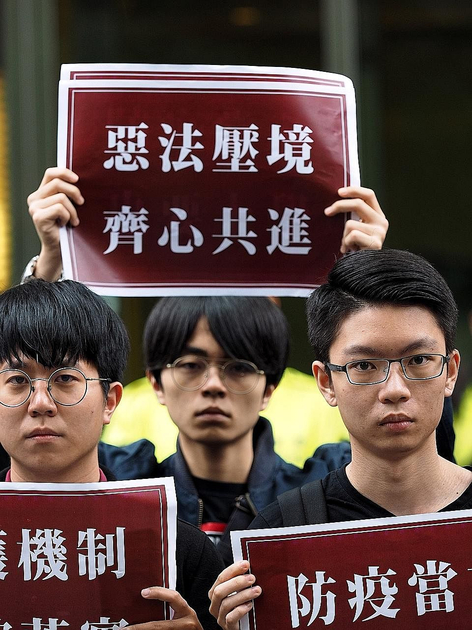 """Members of civic groups in Taiwan holding signs that said """"The national s"""